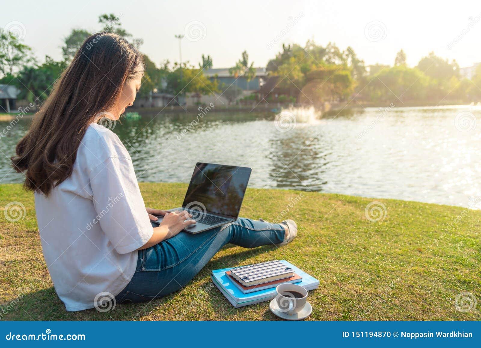 Ritratto di bella donna sorridente che si siede sull erba verde in parco con le gambe attraversate durante il giorno di estate e