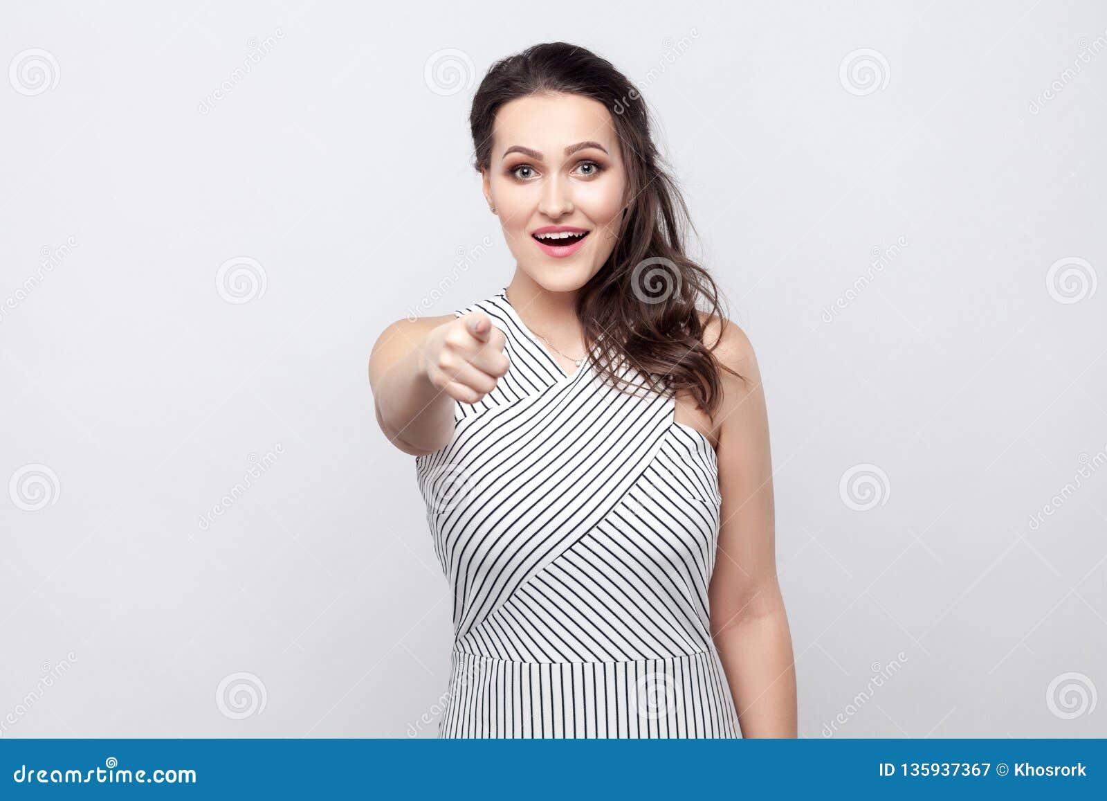 Ritratto di bella giovane donna castana felice stupita con trucco e la condizione a strisce del vestito, esaminante ed indicante