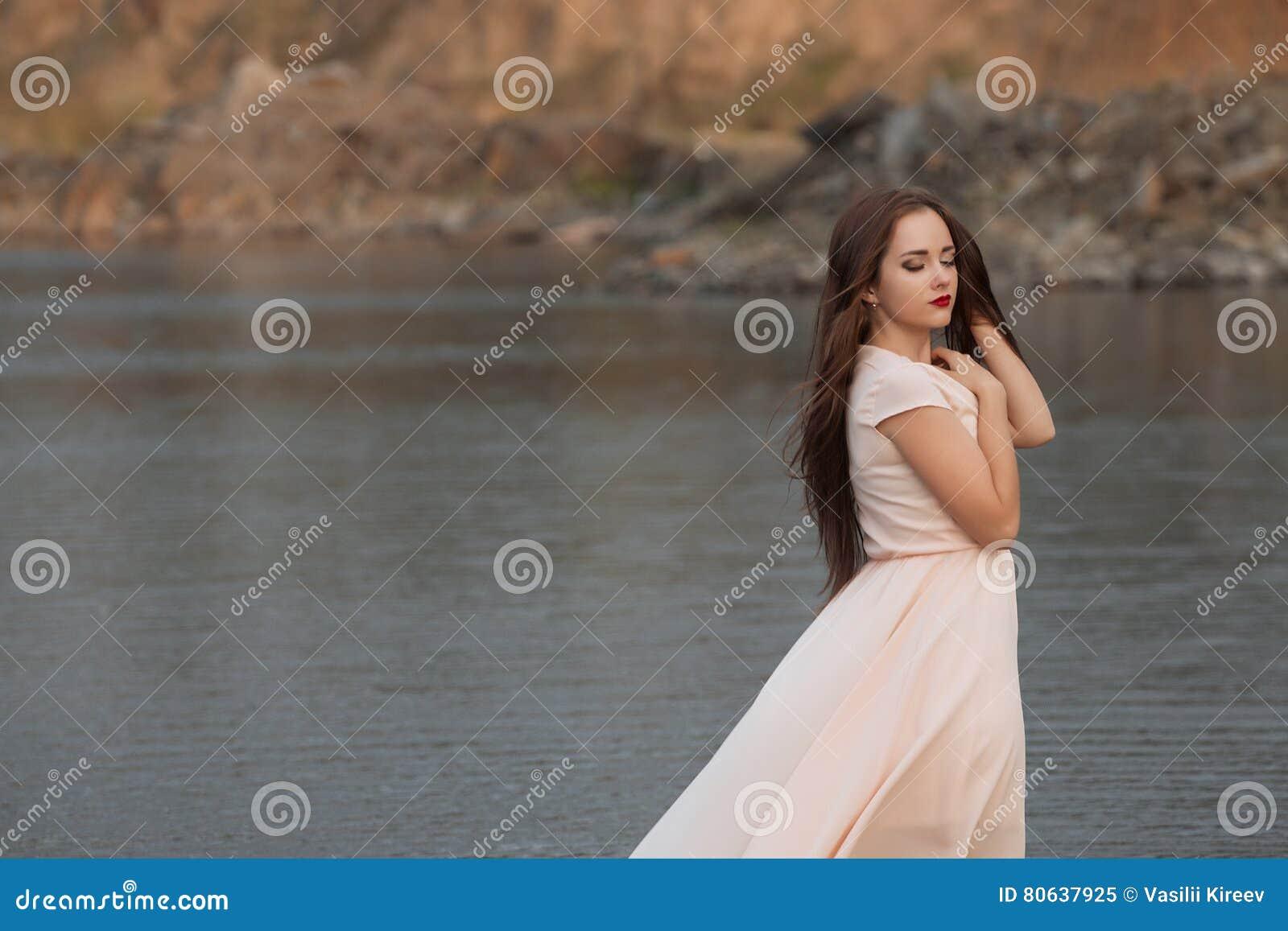 Ritratto di bella giovane donna con il fiore marrone lungo di rosa dei capelli che posa allo studio sopra fondo scuro