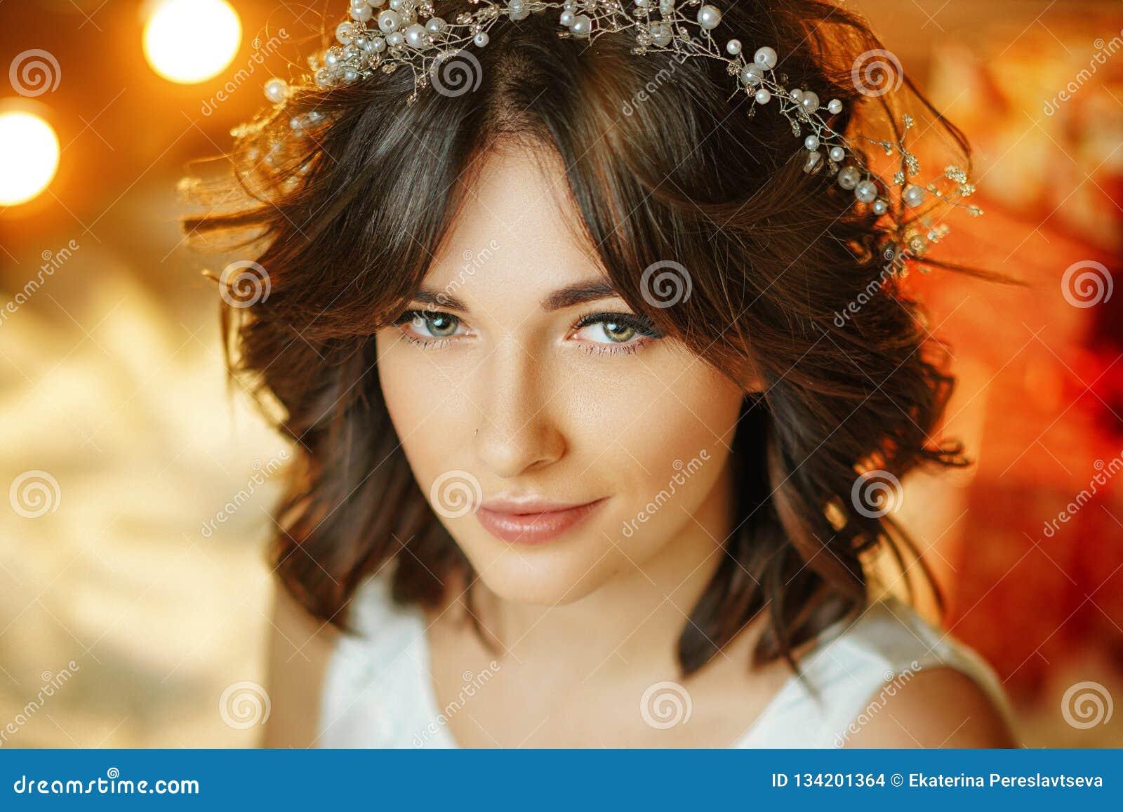 Ritratto di bella giovane donna sui precedenti delle luci, di bello trucco e di designazione