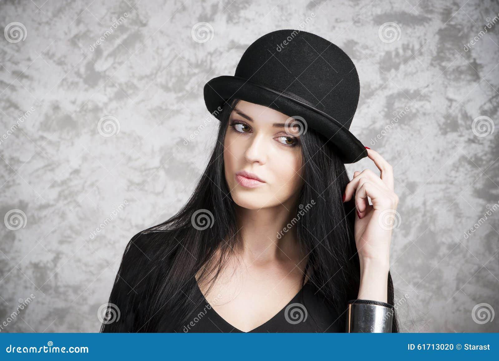 588dd7ff4123 Ritratto di bella giovane donna in un cappello nero di giocatore di bocce e  del vestito