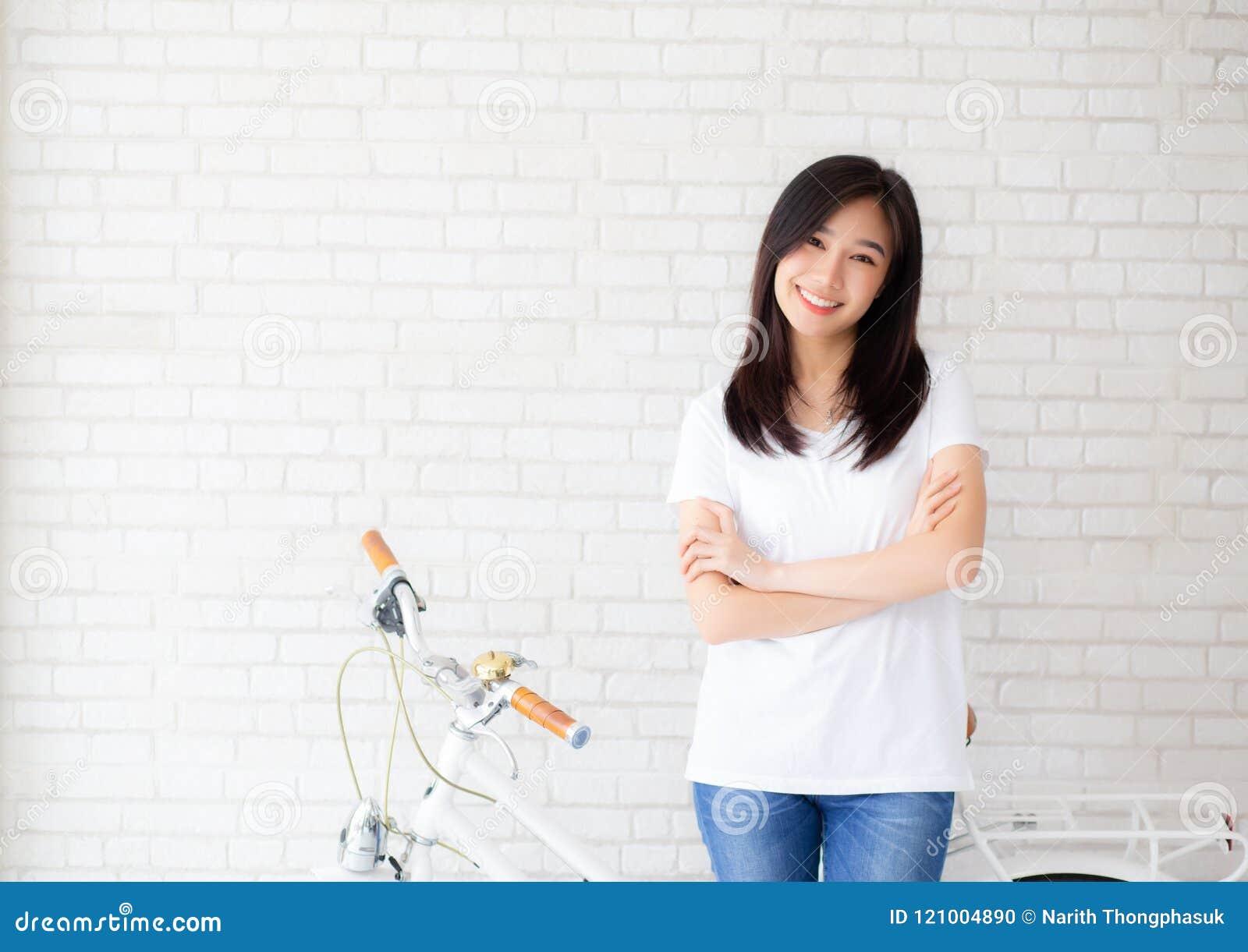 Ritratto di bella giovane felicità asiatica della donna che sta sul fondo grigio del mattone della parete di lerciume di struttur