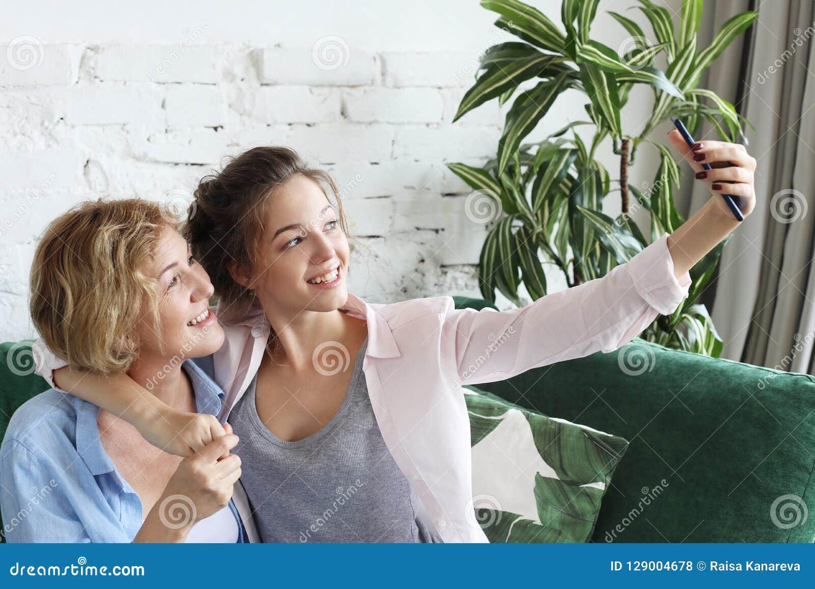 Ritratto di bella madre matura e sua della figlia che fanno un selfie facendo uso dello Smart Phone e che sorridono, domestico e