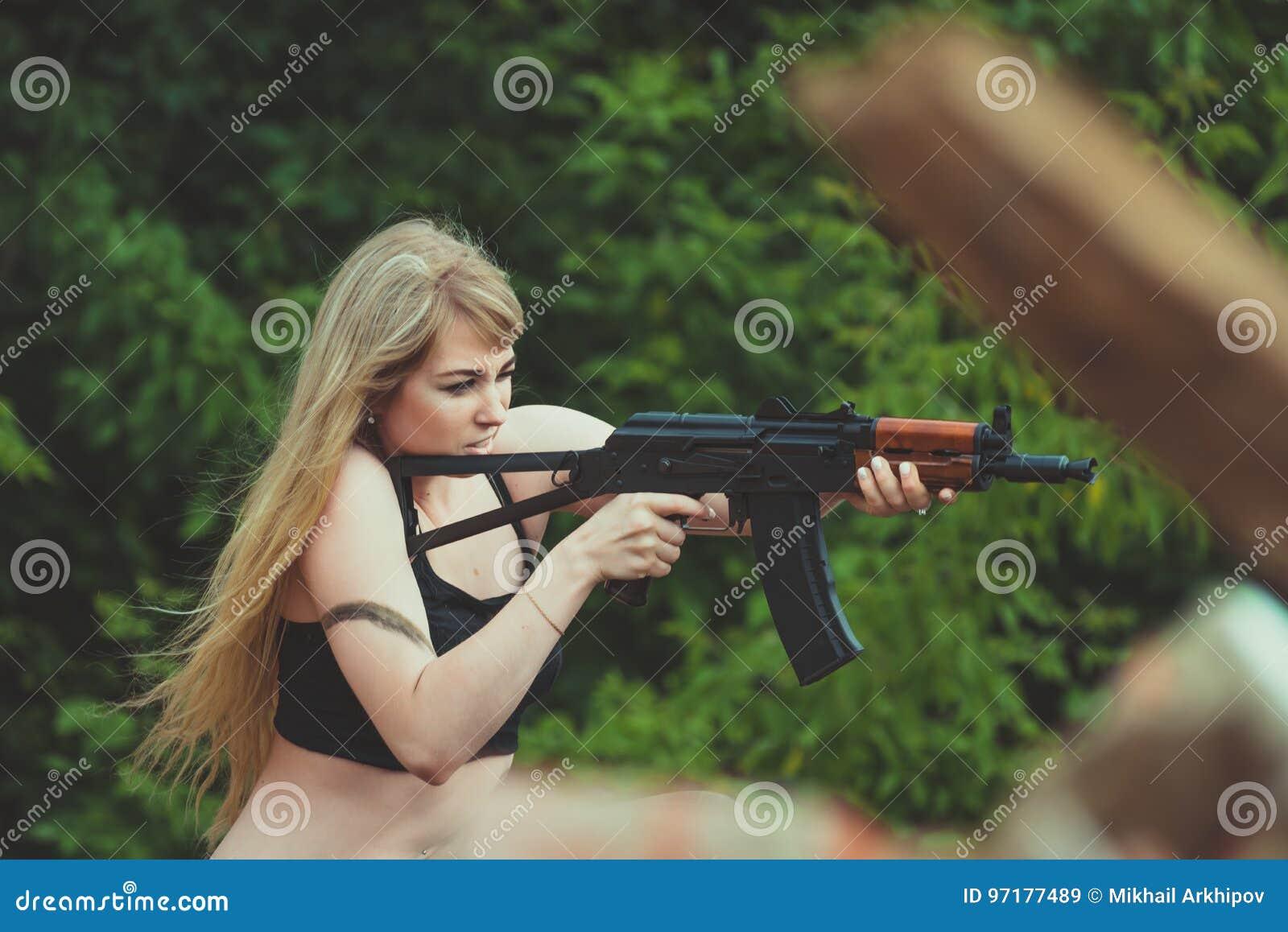 Ritratto di bella ragazza in cammuffamento nelle sue armi durante la a