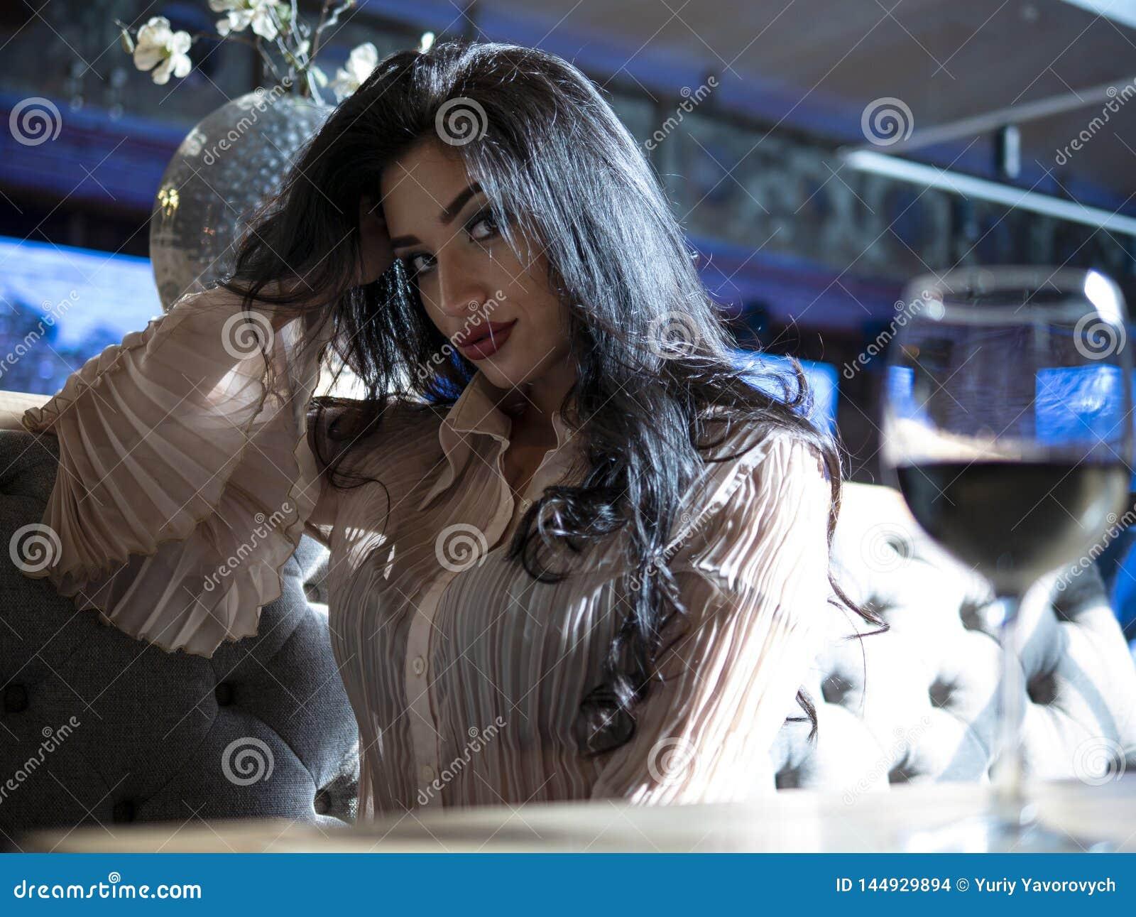 Ritratto di bella ragazza castana che si siede alla tavola con un vetro di vino rosso