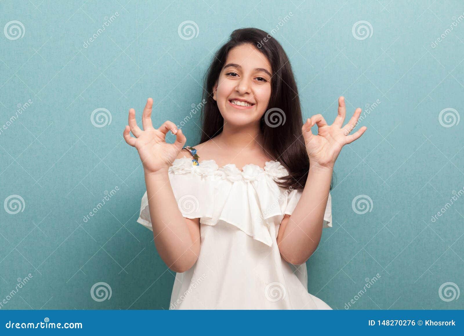 Ritratto di bella ragazza castana felice con capelli diritti lunghi nella condizione bianca del vestito con il segno di approvazi
