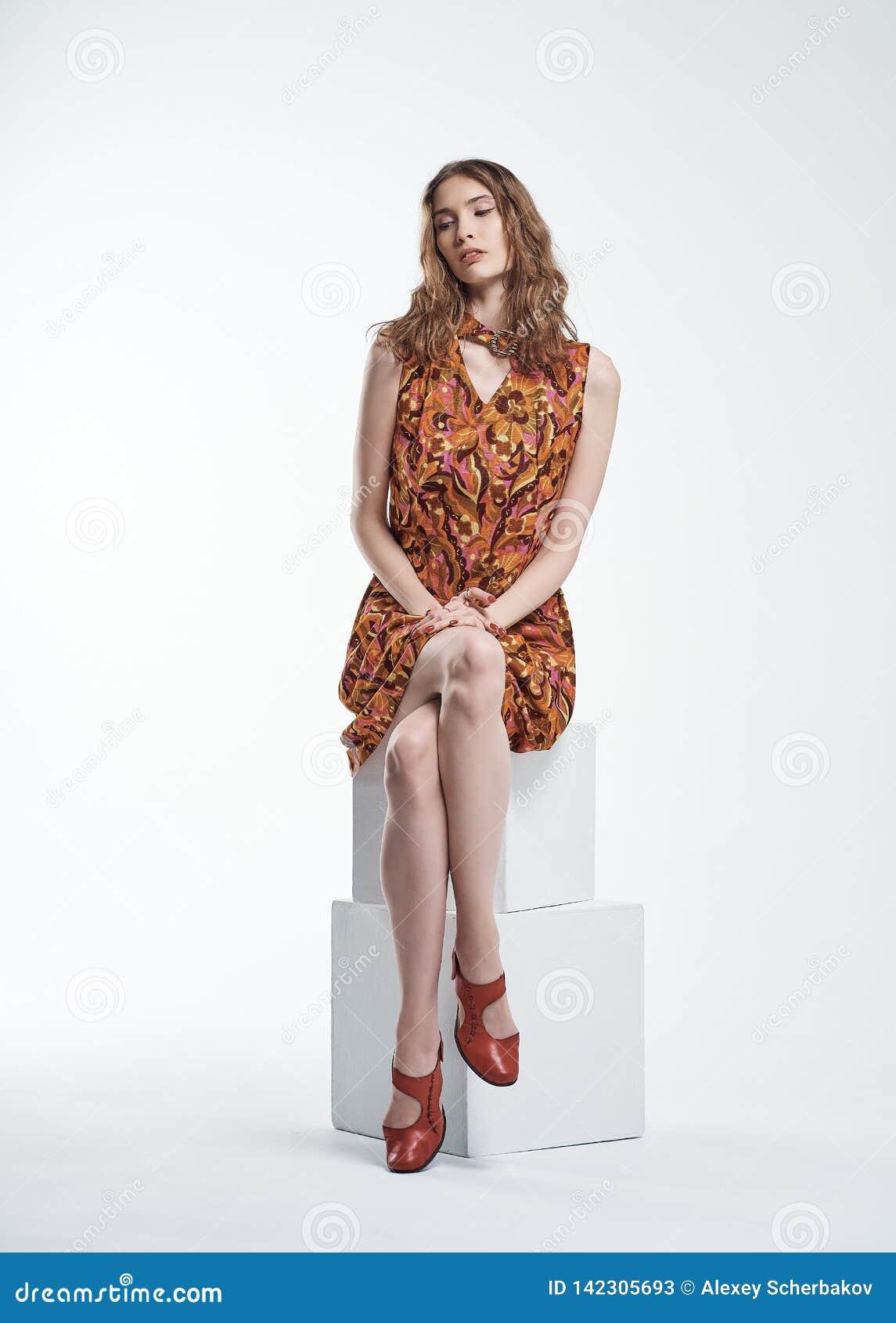 Ritratto di bella ragazza che si siede su un cubo bianco