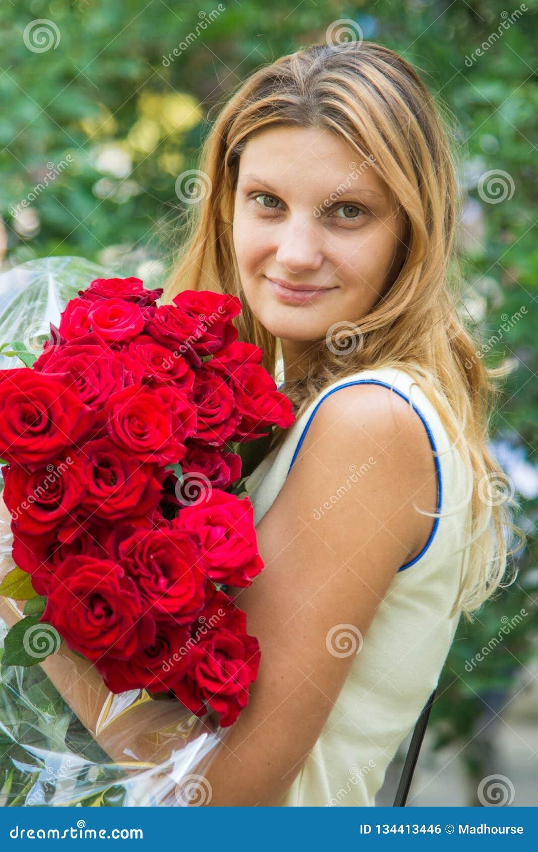 Ritratto di bella ragazza con un mazzo delle rose in sue mani