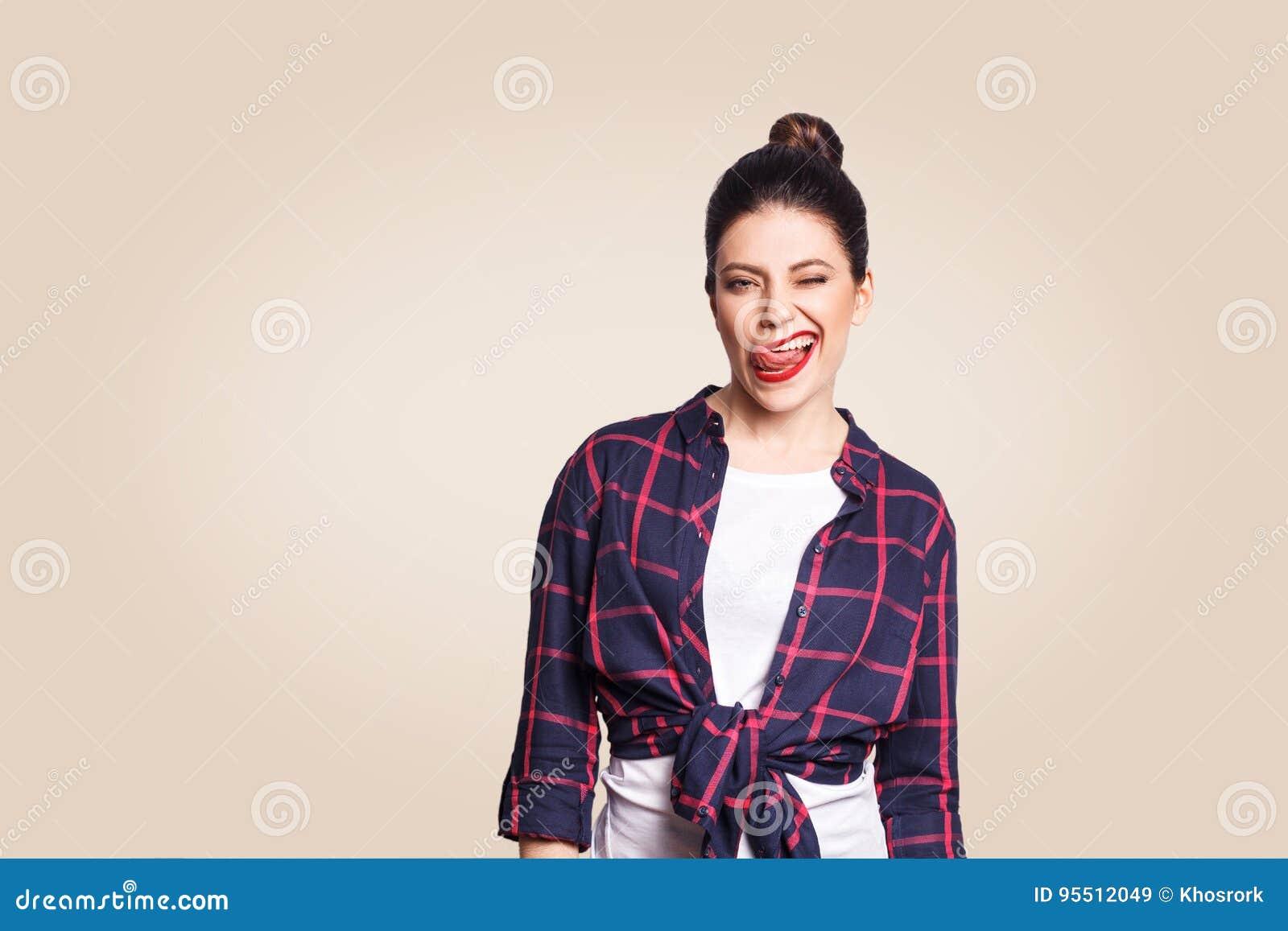 Ritratto di bella ragazza felice nello stile casuale che esamina macchina fotografica con il fronte e lingua fuori e strizzatina