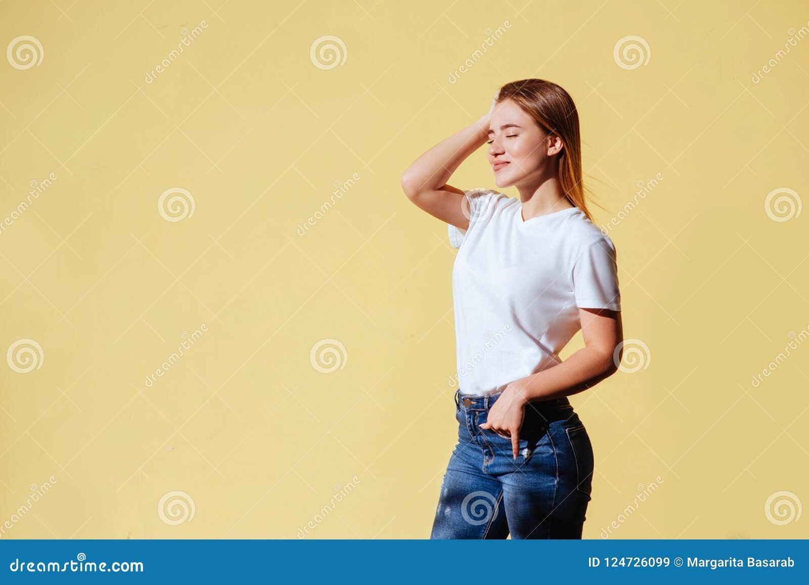 Ritratto di bella ragazza sorridente contro di fondo giallo