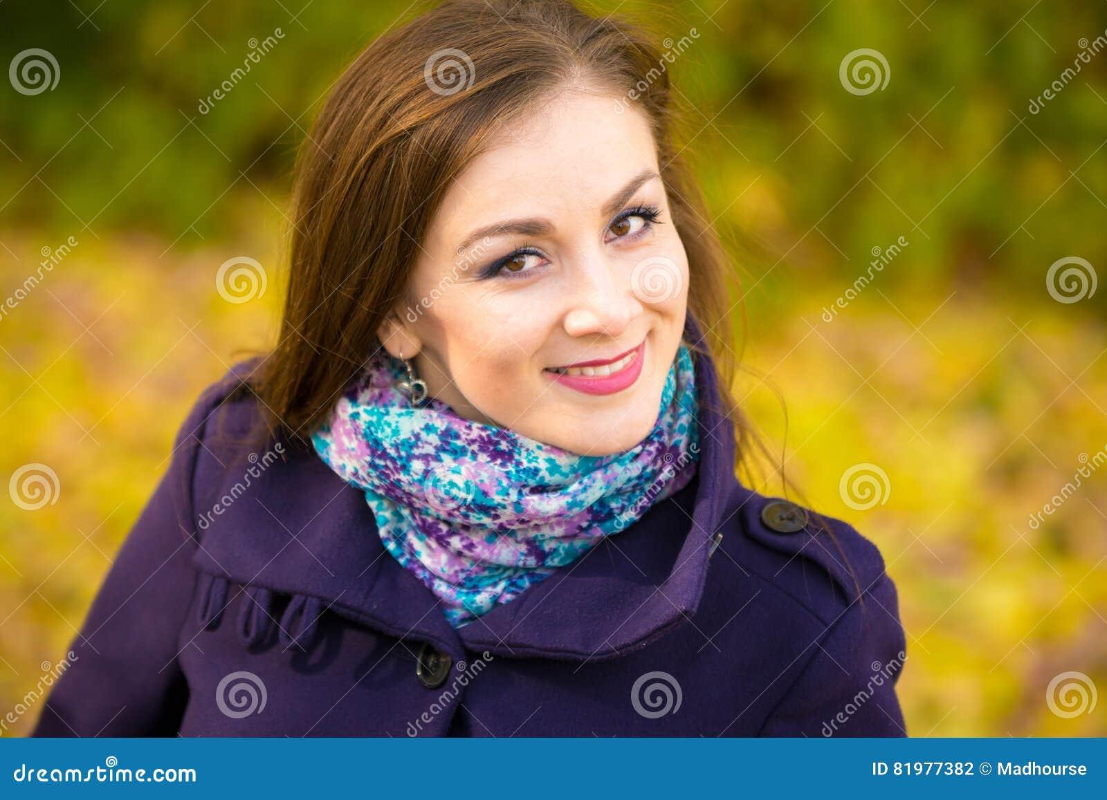 2b58eef11467 Ritratto di bella ragazza sorridente su fondo confuso delle foglie di  autunno