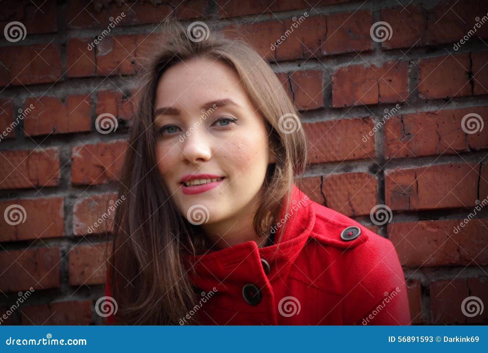 Ritratto di bella ragazza in un cappotto rosso su un backg del muro di mattoni
