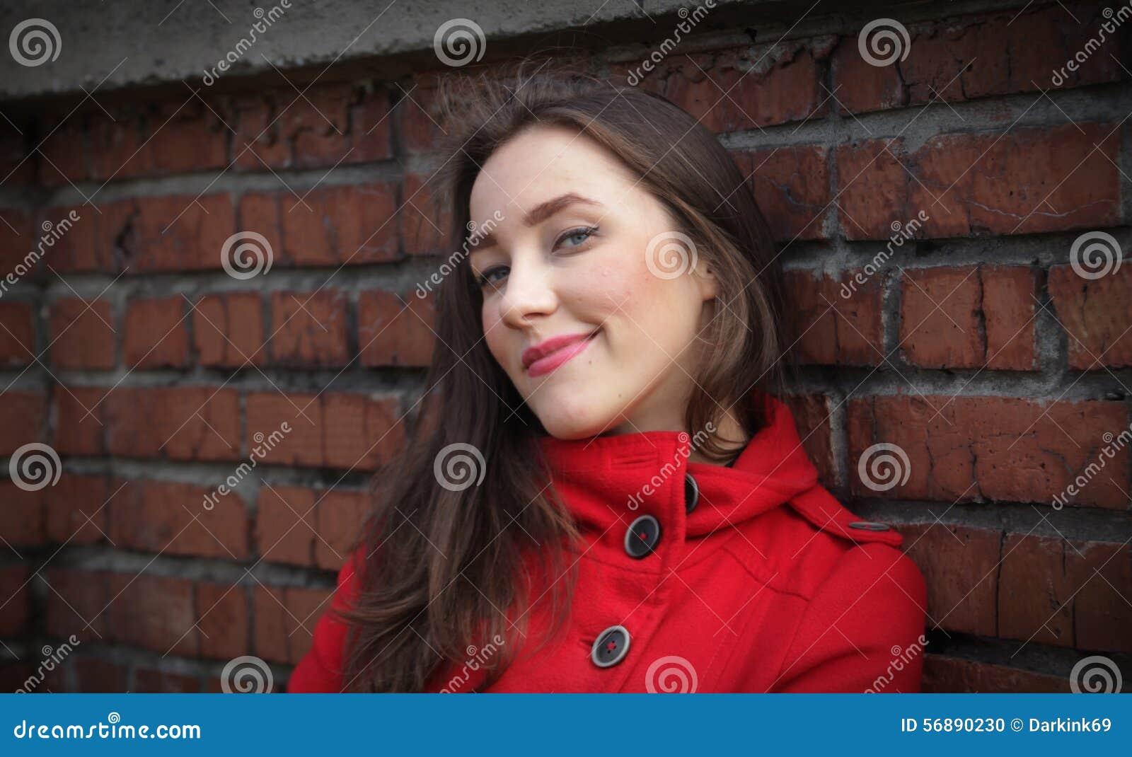 Ritratto di bella ragazza in un cappotto rosso su un muro di mattoni