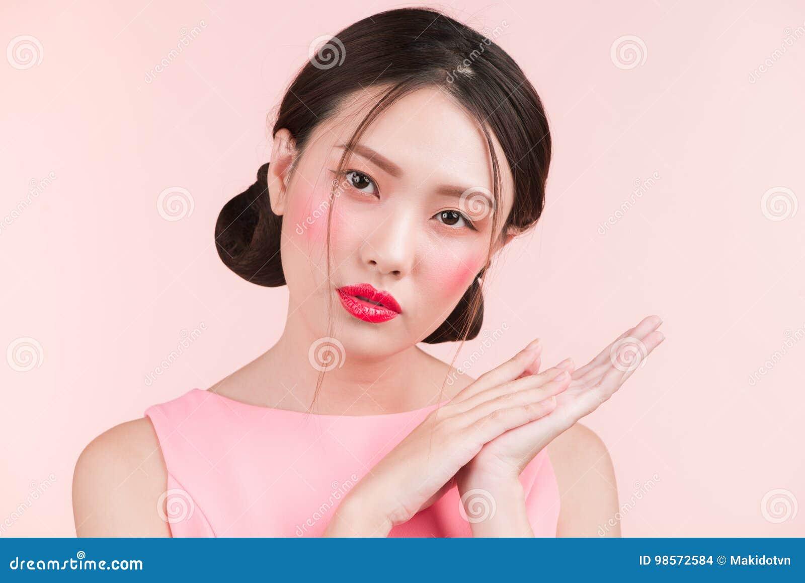 Ritratto di bellezza del fronte asiatico femminile sopra il fondo rosa di colore