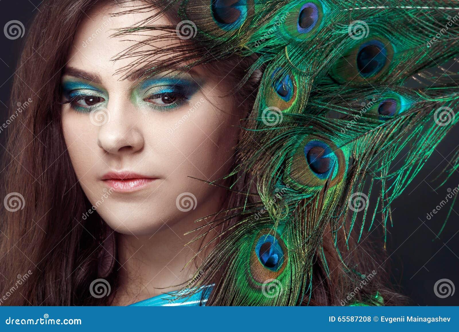 Ritratto di bellezza di bella ragazza che copre gli occhi di piuma del pavone Piume creative del pavone di trucco attraente