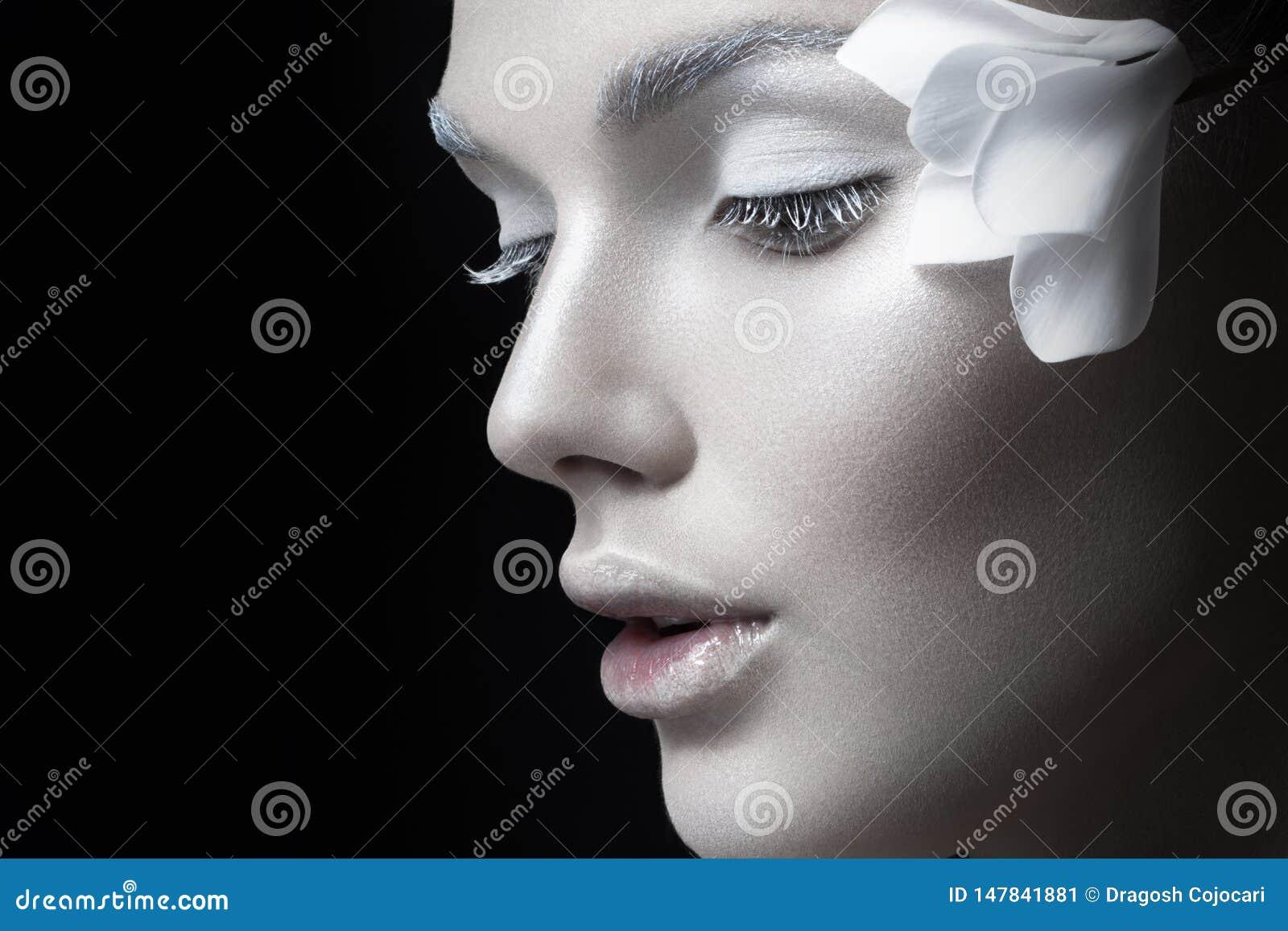 Ritratto di bellezza , ragazza con trucco bianco, fiori del anf vicino all orecchio Trucco di concetto, cosmetici, su fondo nero