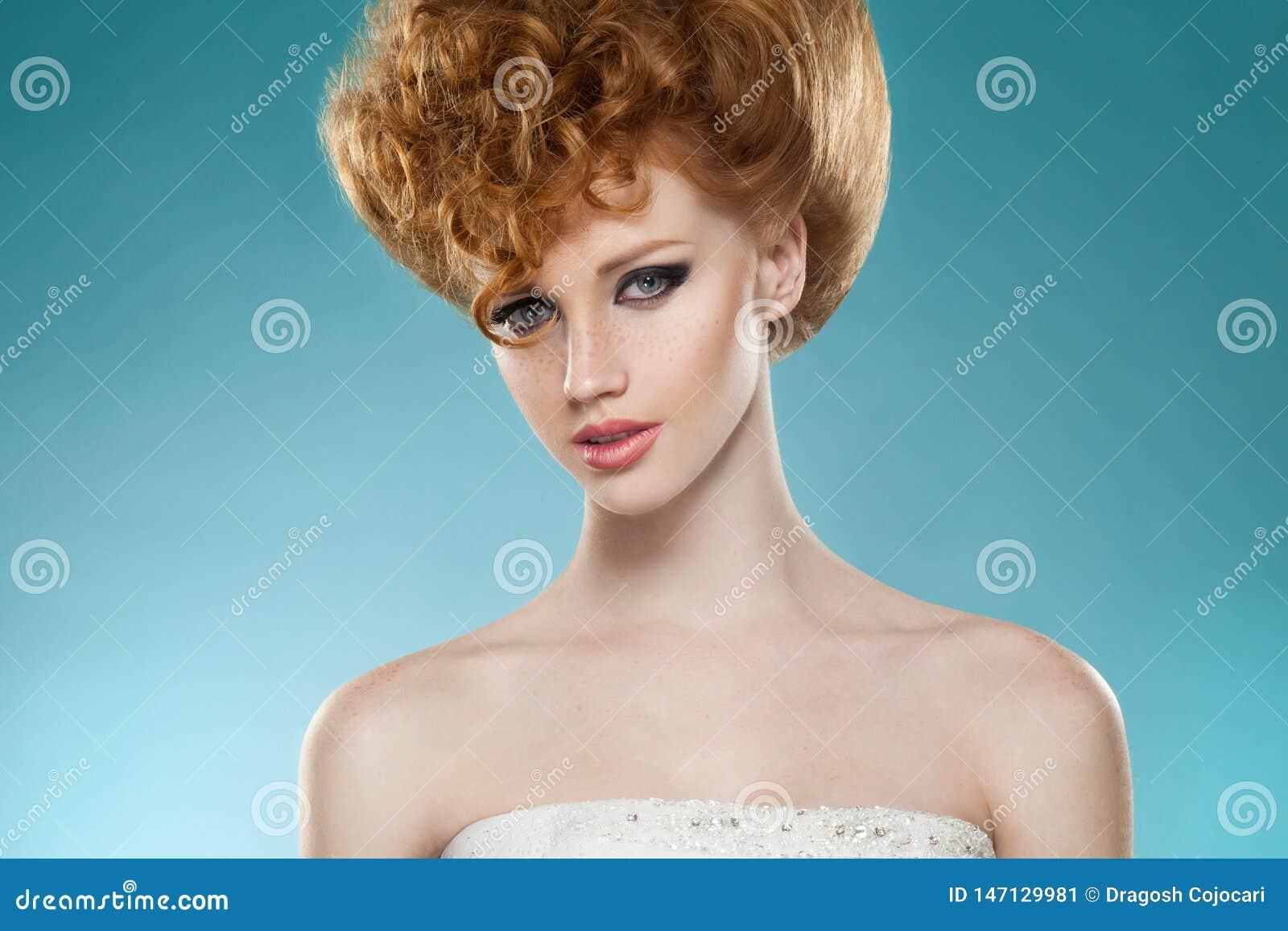 Ritratto di bellezza di una ragazza hairred rossa con hairdressed e macchiolina, con le spalle nude, isolate su un fondo blu