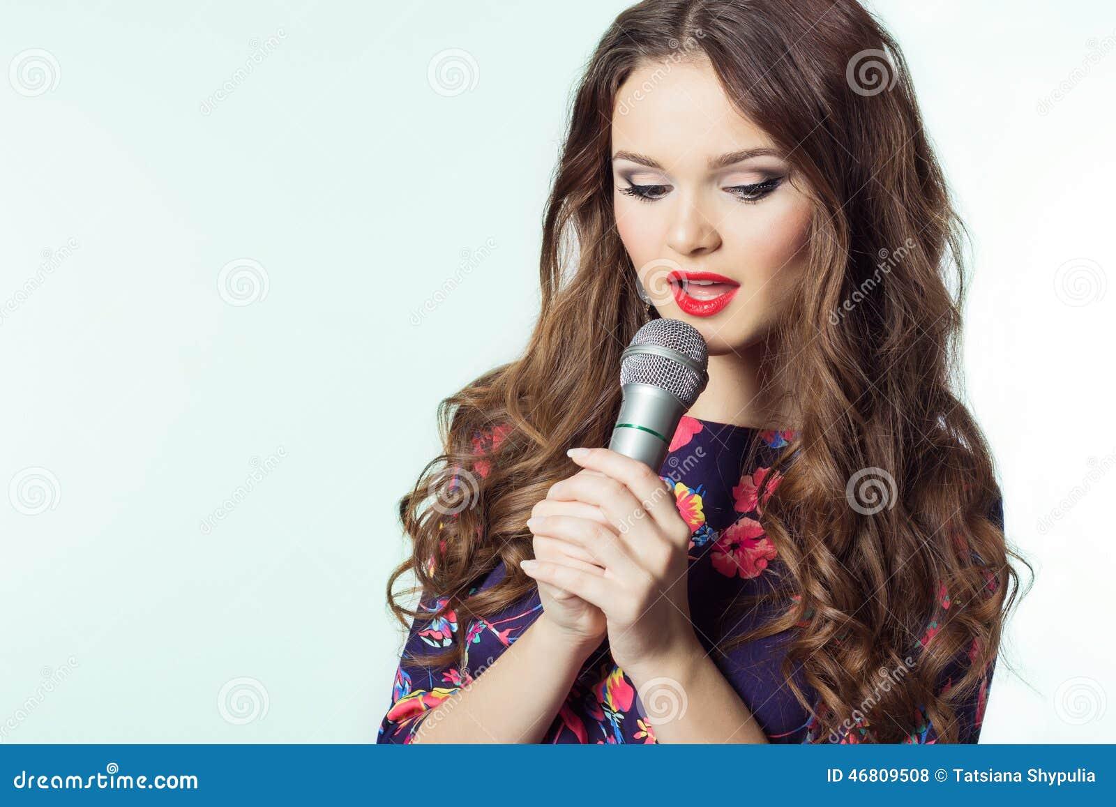 Ritratto di bello cantante elegante della ragazza castana con capelli lunghi con un microfono in sua mano che canta una canzone