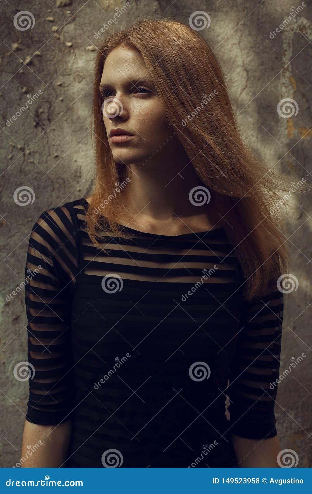 Ritratto di bello modello dai capelli rossi dello zenzero con le lentiggini sul suo fronte che posa in un vestito da cocktail ner
