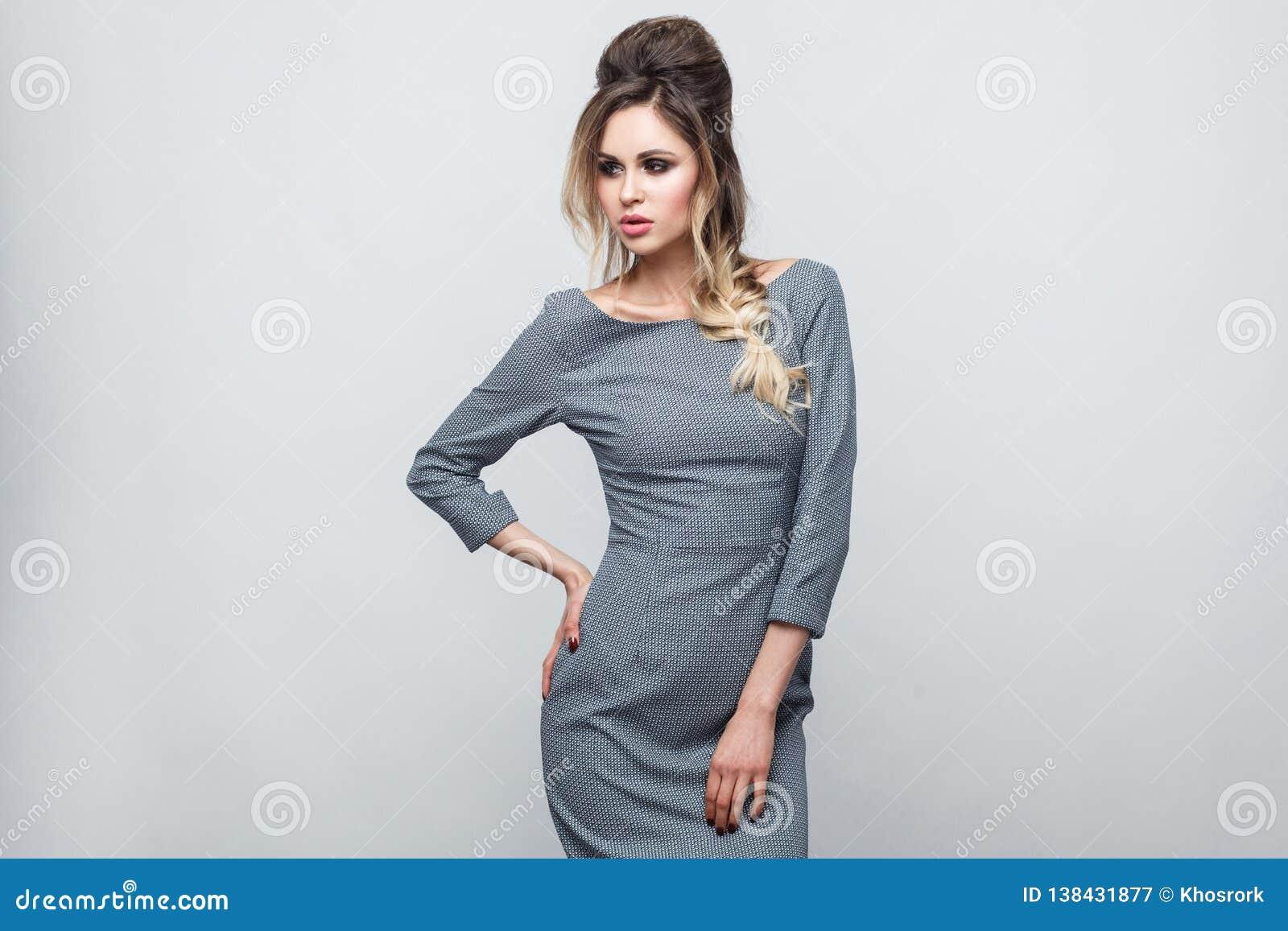 Ritratto di bello modello di moda attraente in vestito grigio con la condizione dell acconciatura e di trucco, posante con la man