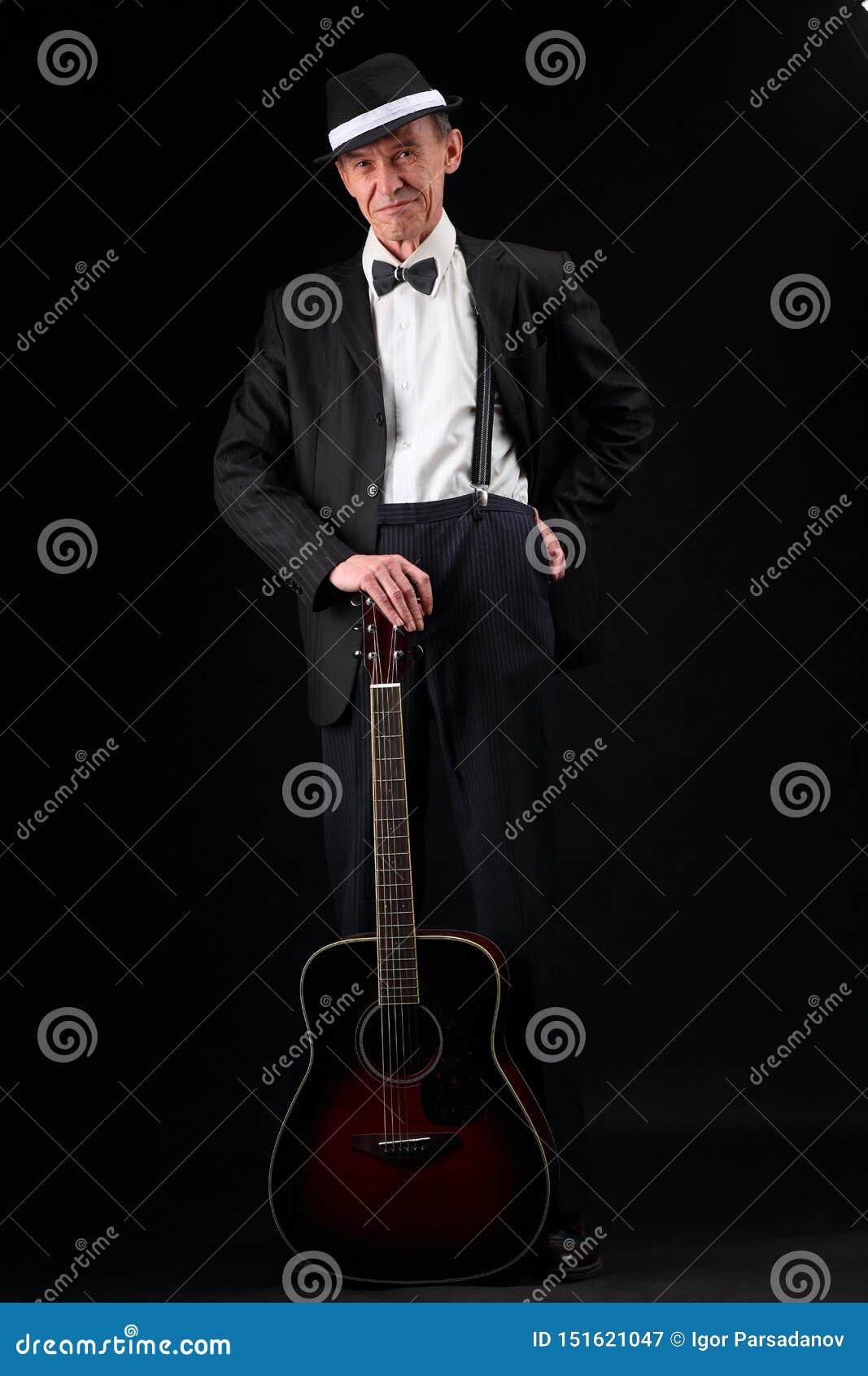 Ritratto di crescita di un musicista anziano con una chitarra