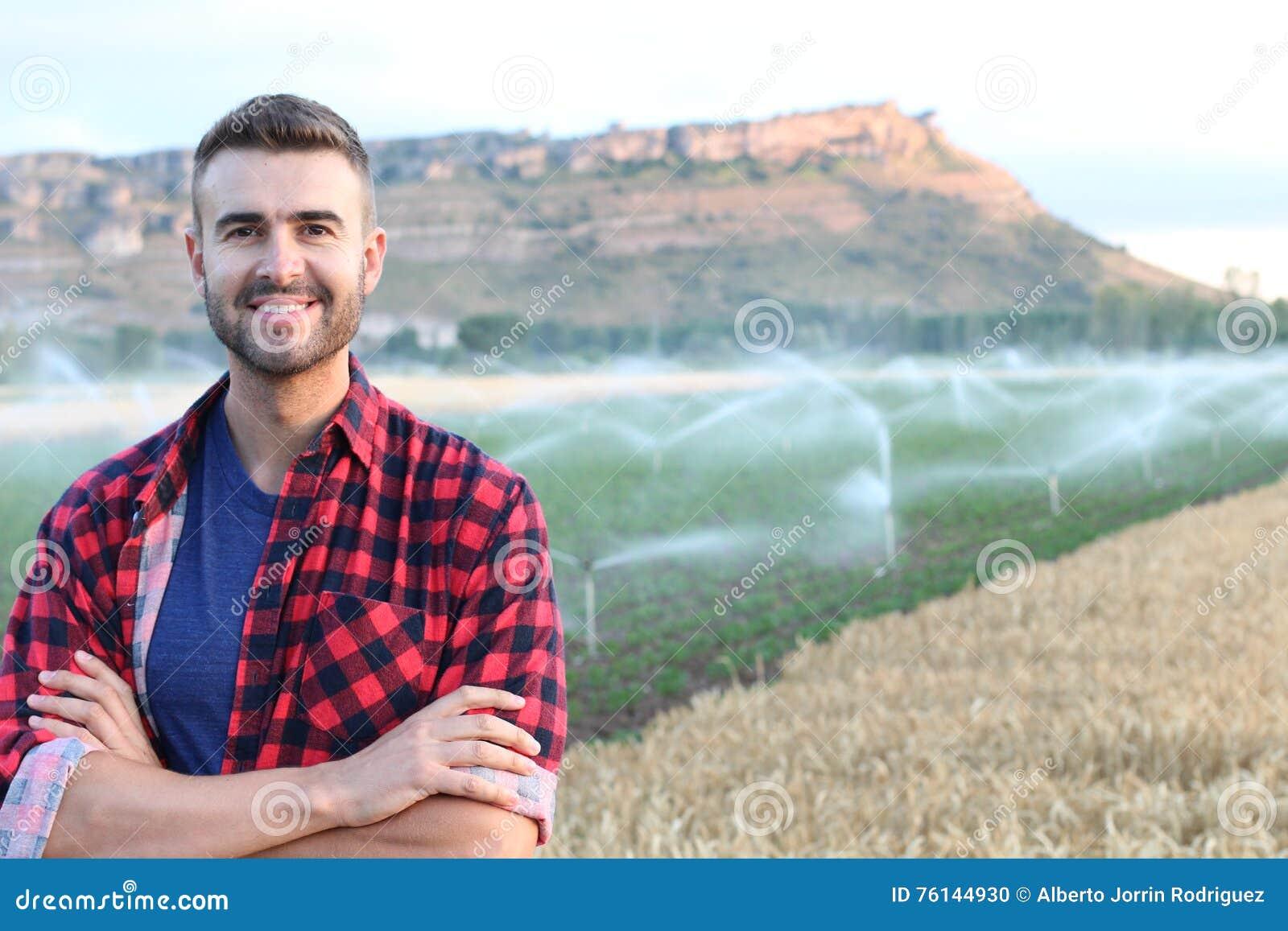 Ritratto di giovane agricoltore bello che sorride sul terreno coltivabile