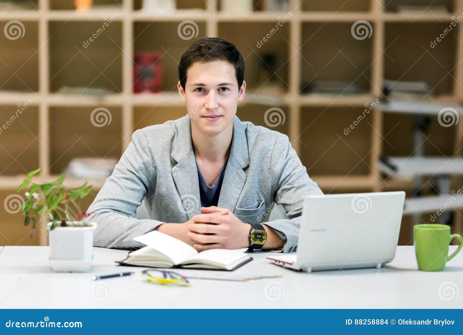 Ritratto di giovane apprendista corporativo al posto di lavoro accogliente