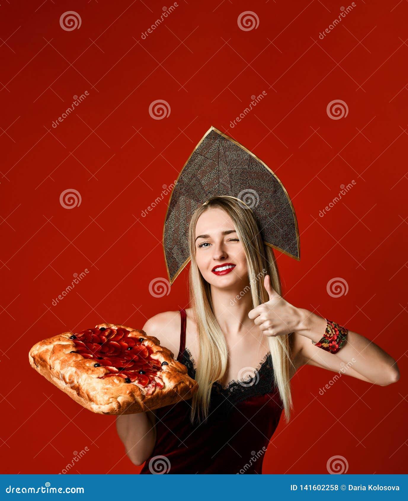 Ritratto di giovane bella bionda che tiene una crostata di ciliege casalinga deliziosa