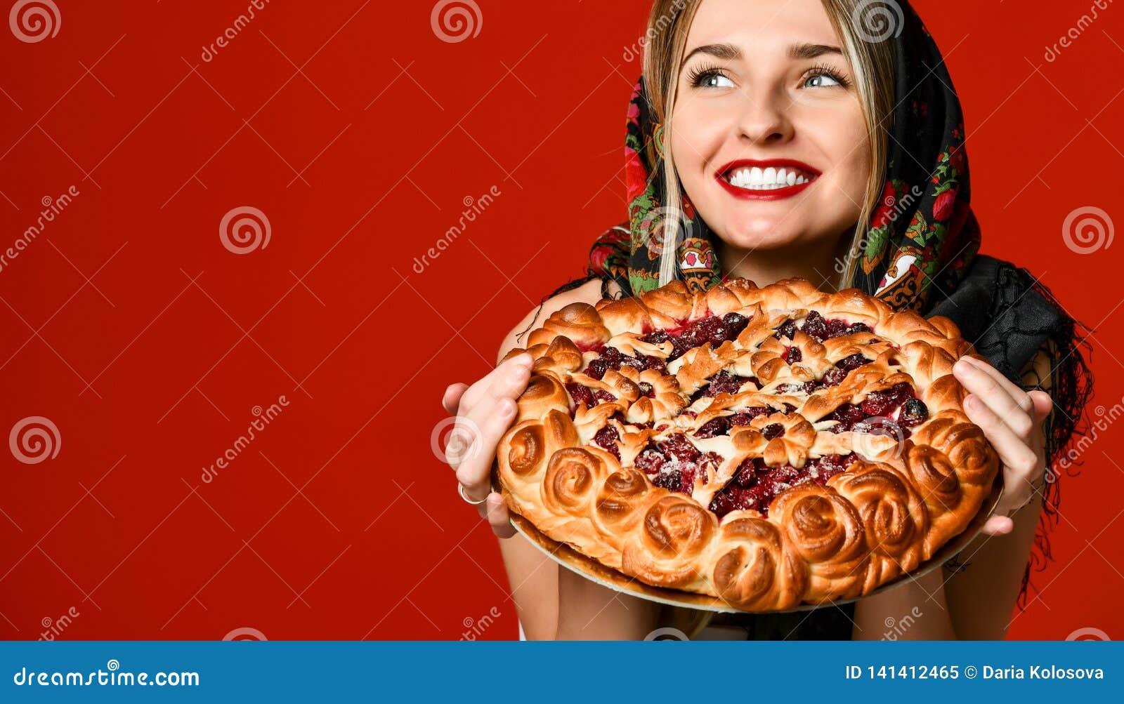 Ritratto di giovane bella bionda in foulard che tiene una crostata di ciliege casalinga deliziosa