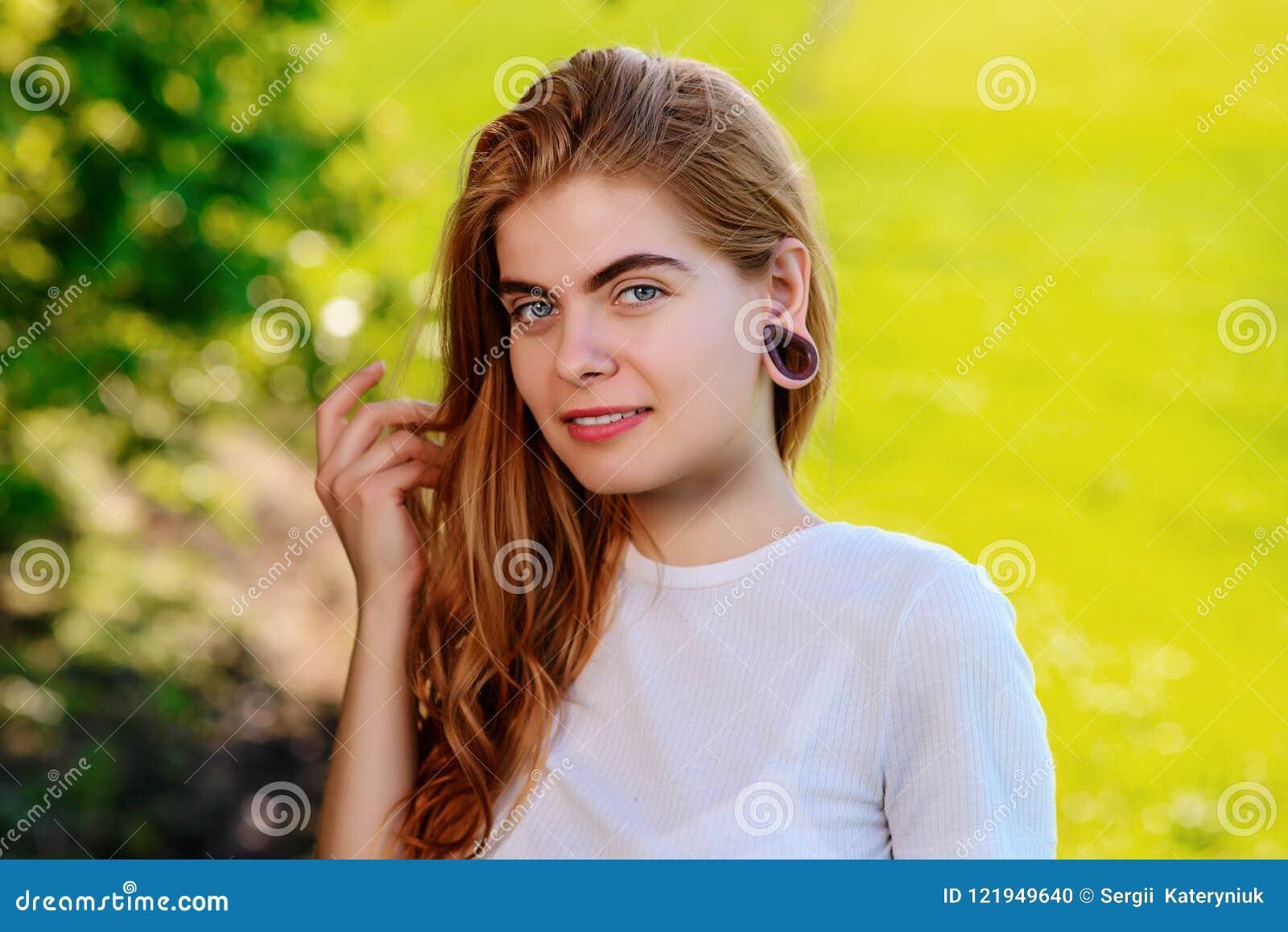 Ritratto di giovane bella donna con i tunnel di legno nella sua e