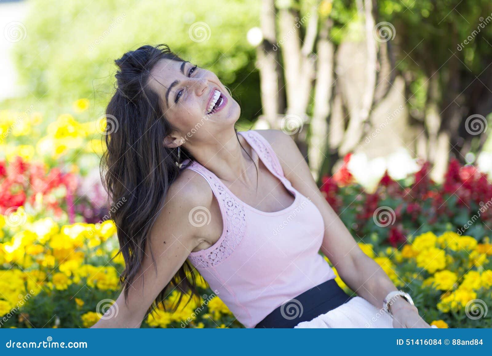 Ritratto di giovane bella donna di modo che ride su un fondo dei fiori