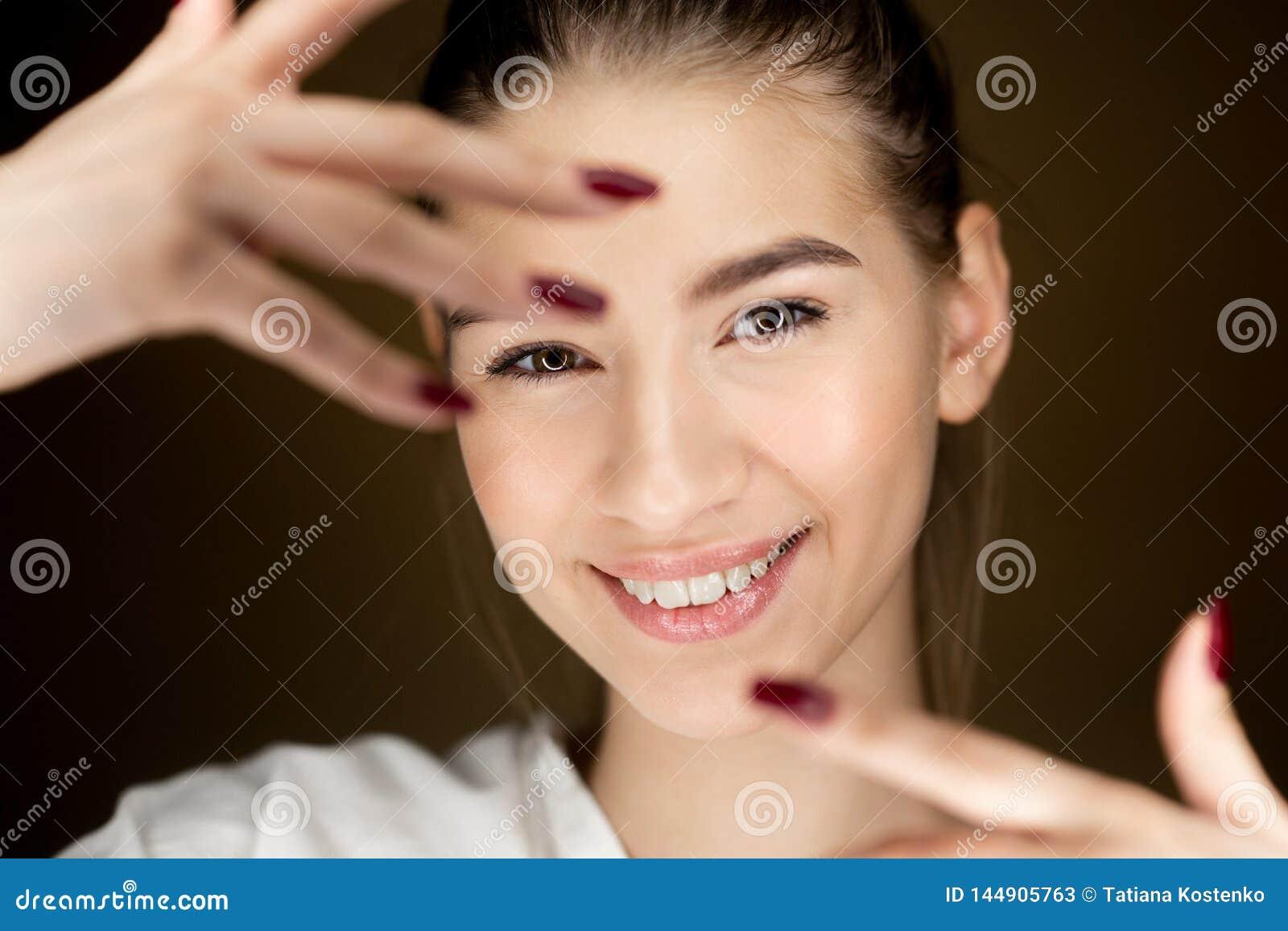 Ritratto di giovane bella ragazza castana con trucco naturale che tiene le sue dita davanti al suo fronte