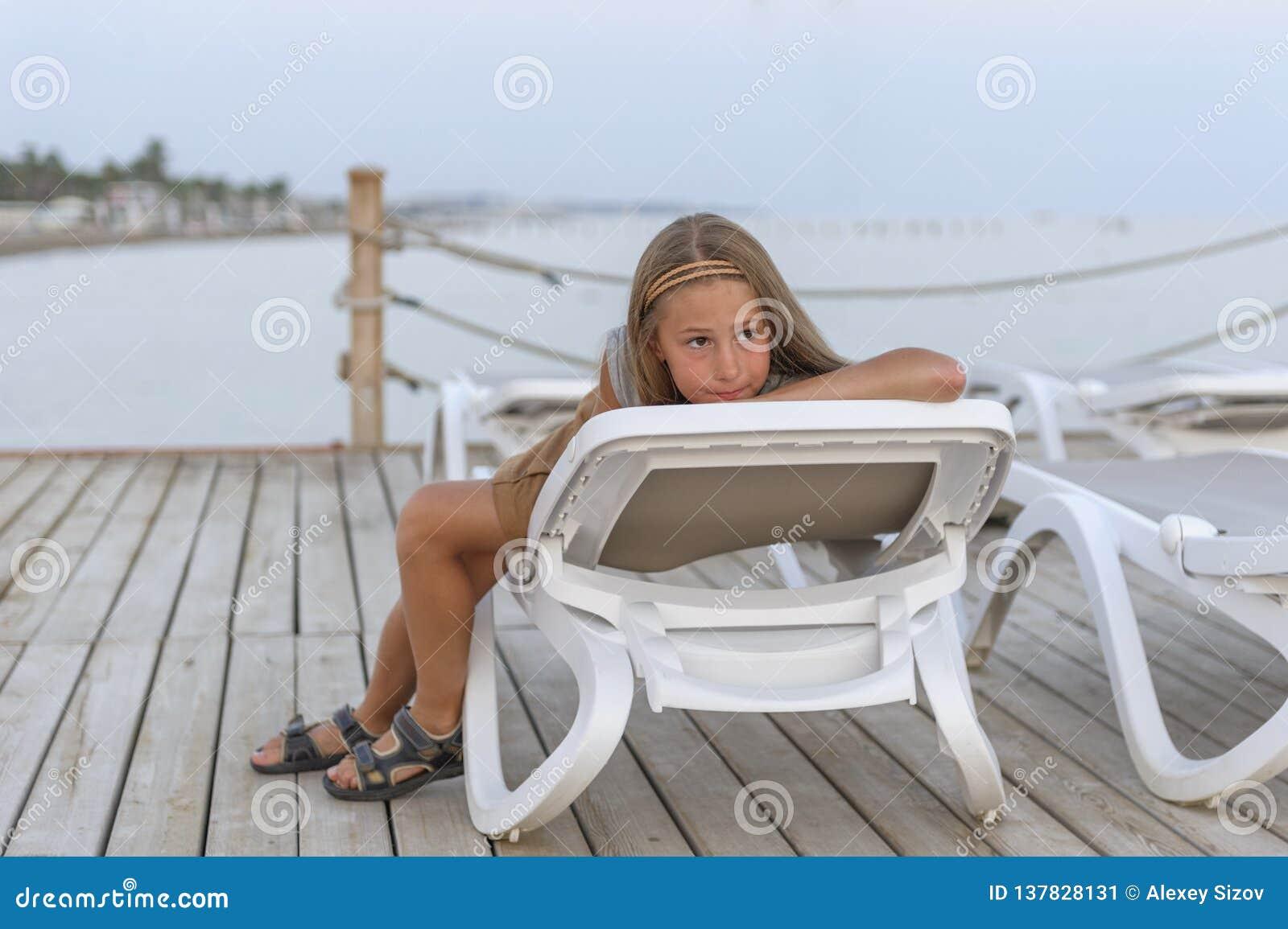 Ritratto di giovane branchia graziosa che esamina macchina fotografica che si trova sulla chaise-lounge del sole