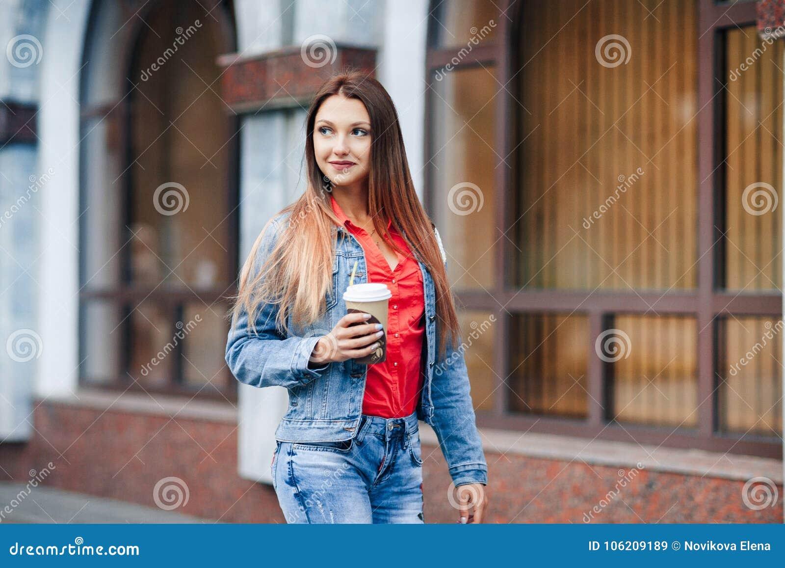 Ritratto di giovane donna alla moda felice in blue jeans e camicia rossa che cammina nel centro urbano e nel caffè bevente