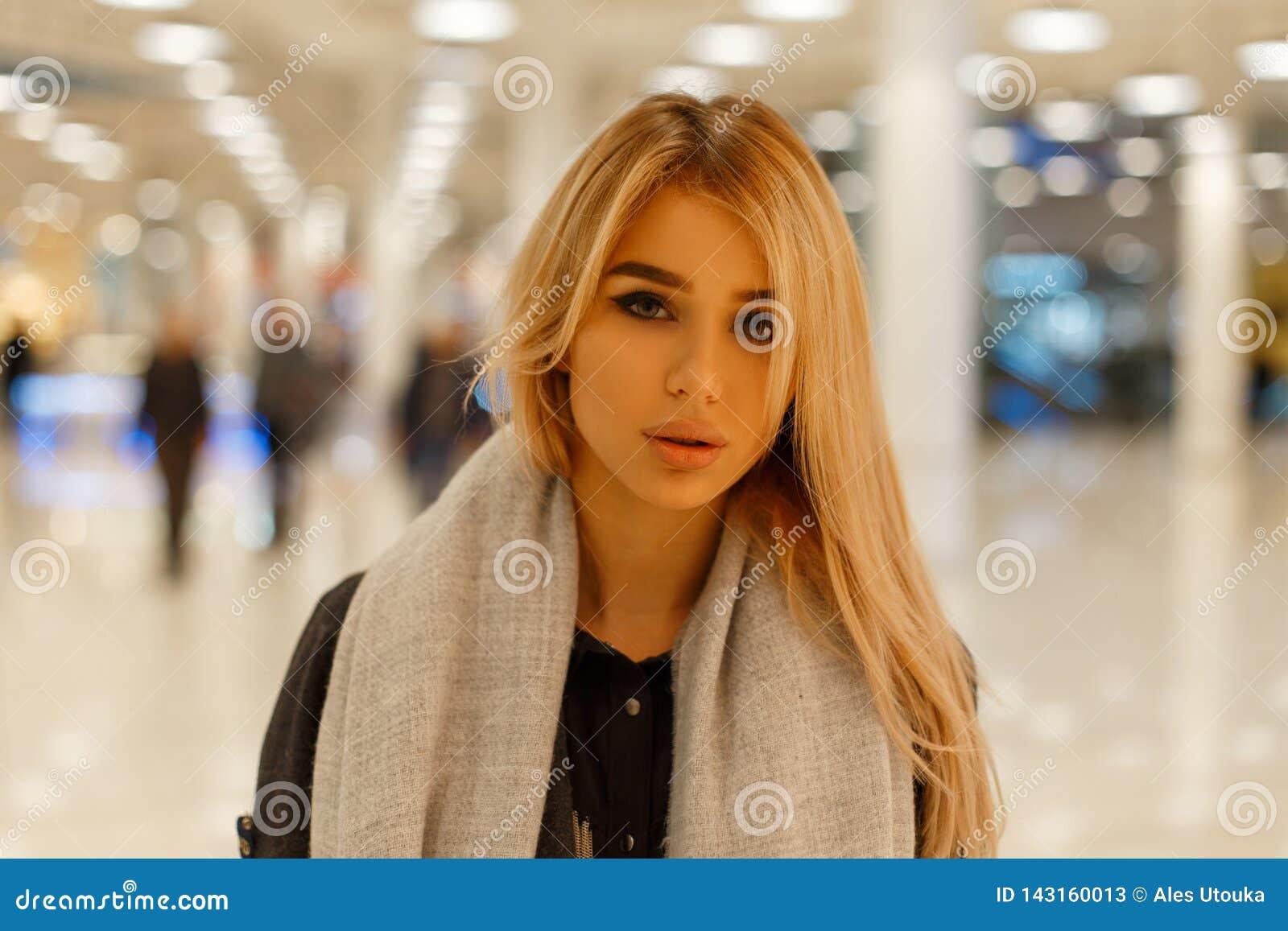 Ritratto di giovane donna bionda sveglia attraente con le labbra sexy con i bei occhi grigi in un cappotto in una sciarpa d annat