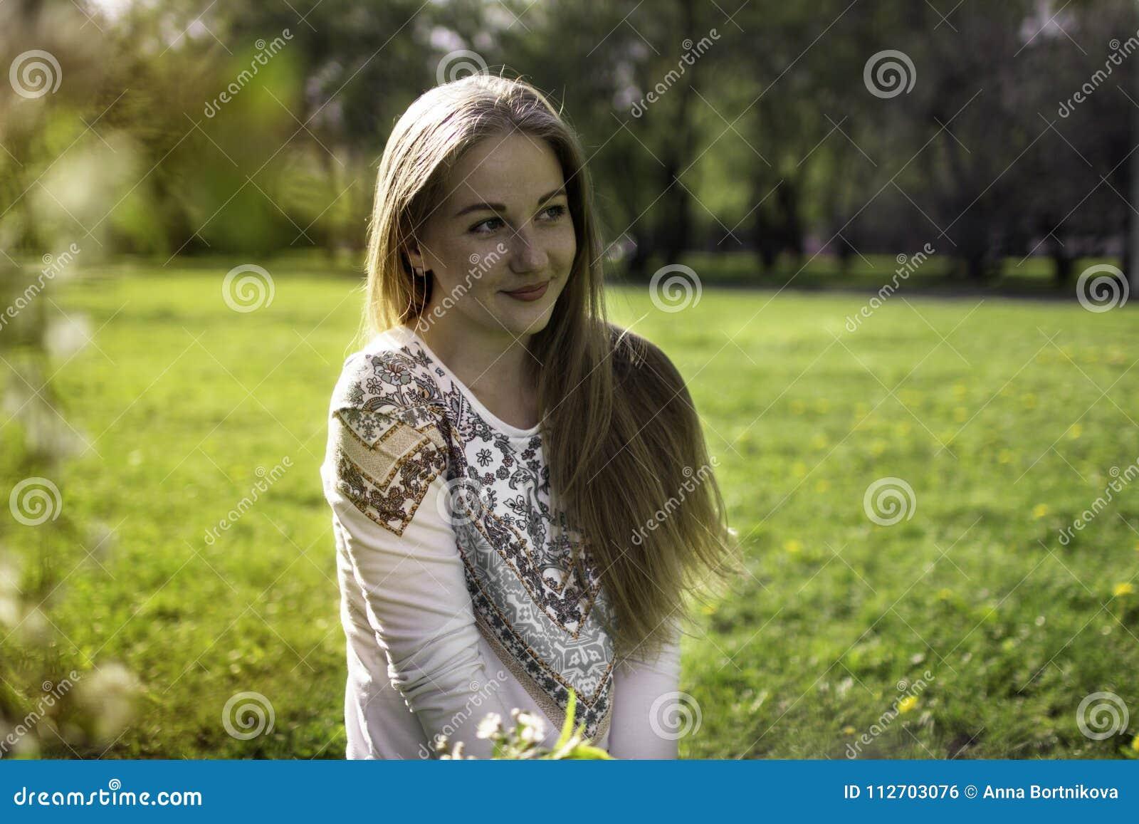 Ritratto di giovane donna bionda in una foresta della molla e in sunli