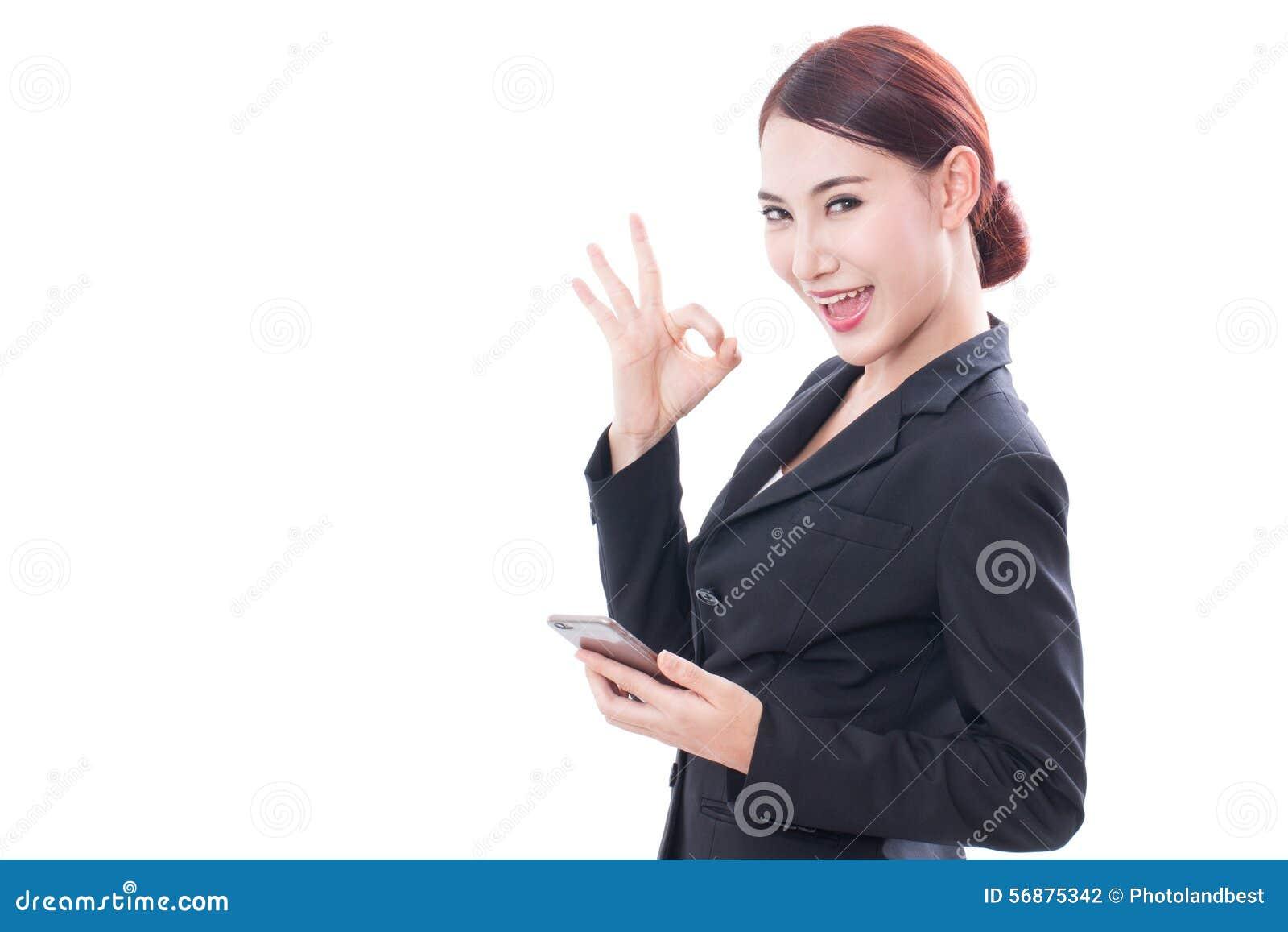 Ritratto di giovane donna di affari che per mezzo di un telefono cellulare e mostrando segno giusto