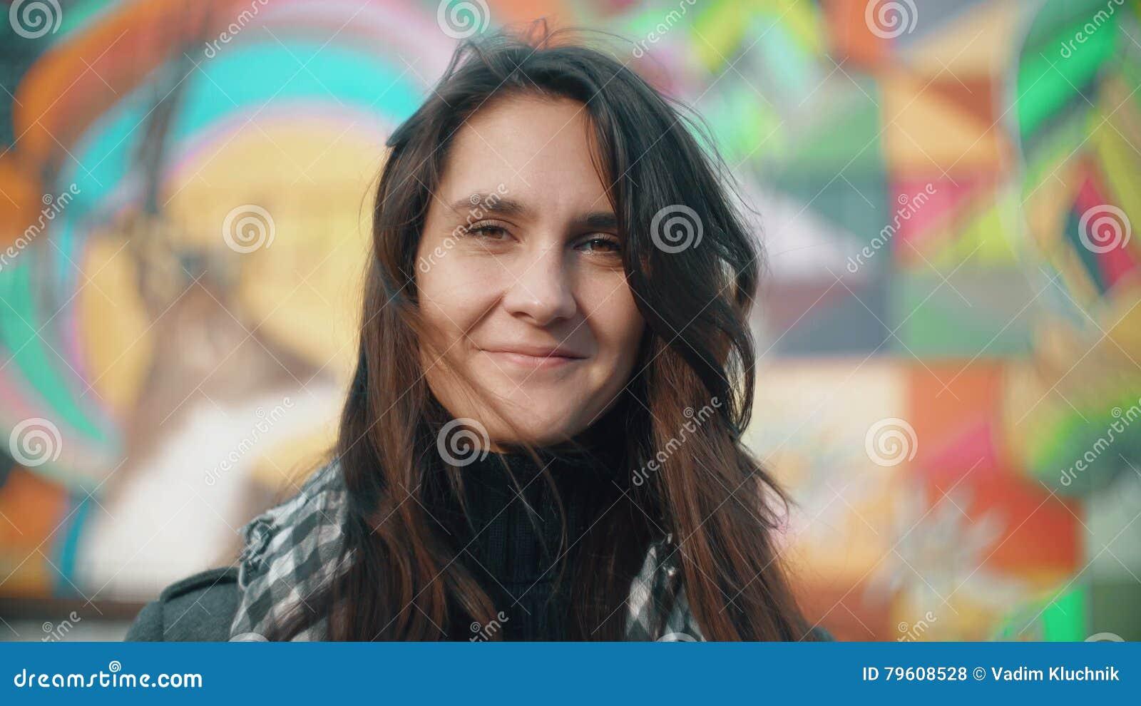 Ritratto di giovane donna sorridente nei raggi del tramonto su un fondo variopinto Primo piano 4K