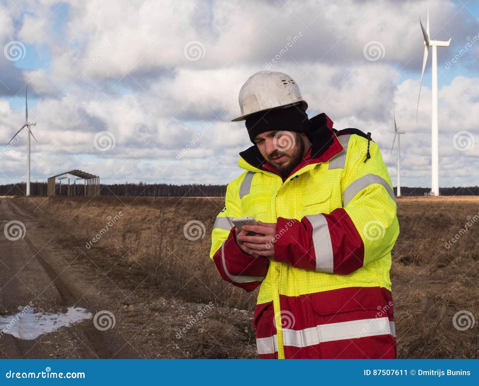 Ritratto di giovane ingegnere che lavora al telefono cellulare all aperto in casco e rivestimento riflettente