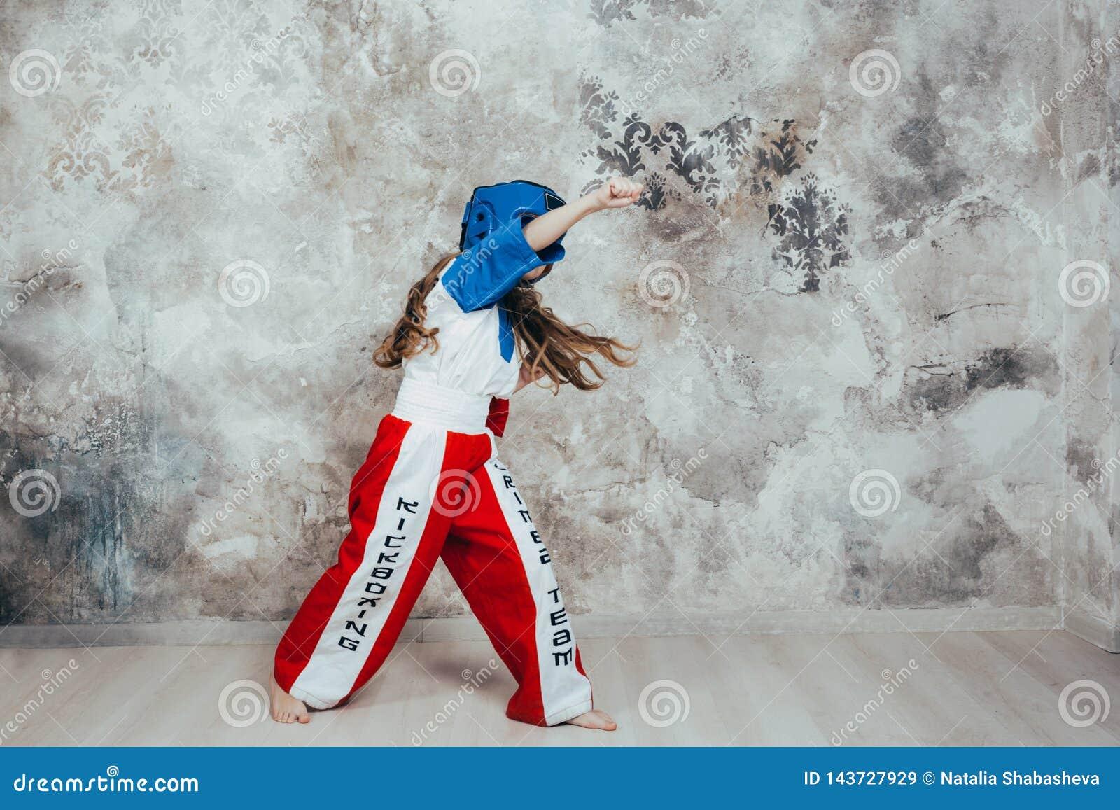 Ritratto di giovane ragazza femminile sorridente del taekwondo contro una parete di lerciume