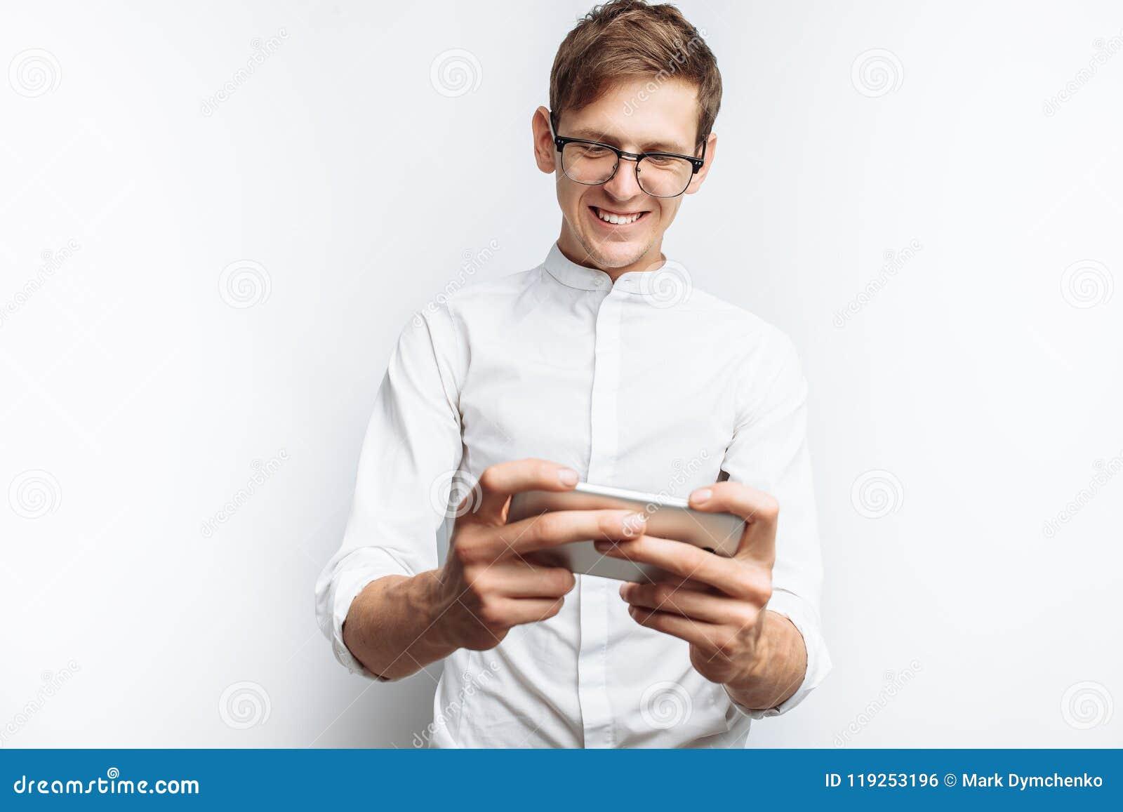 Ritratto di giovane tipo attraente in vetri che giocano sul telefono, in camicia bianca isolata su fondo bianco, per annunciare,