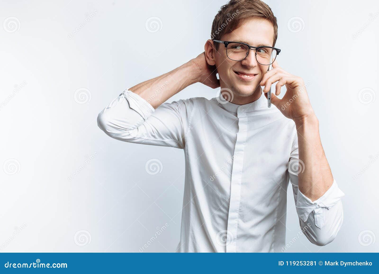 Ritratto di giovane tipo attraente in vetri che parla sul telefono e che descrive gioia, in camicia bianca isolata su fondo bianc