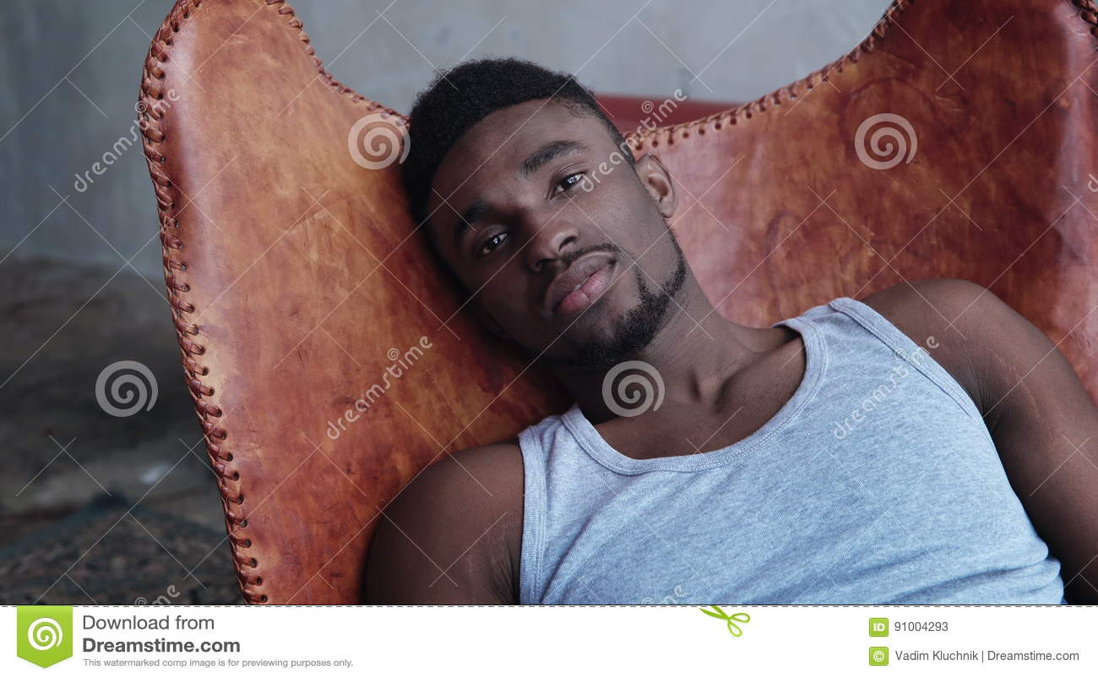 Ritratto di giovane uomo africano bello che si siede sulla sedia di cuoio e che esamina macchina fotografica Maschio di modello s