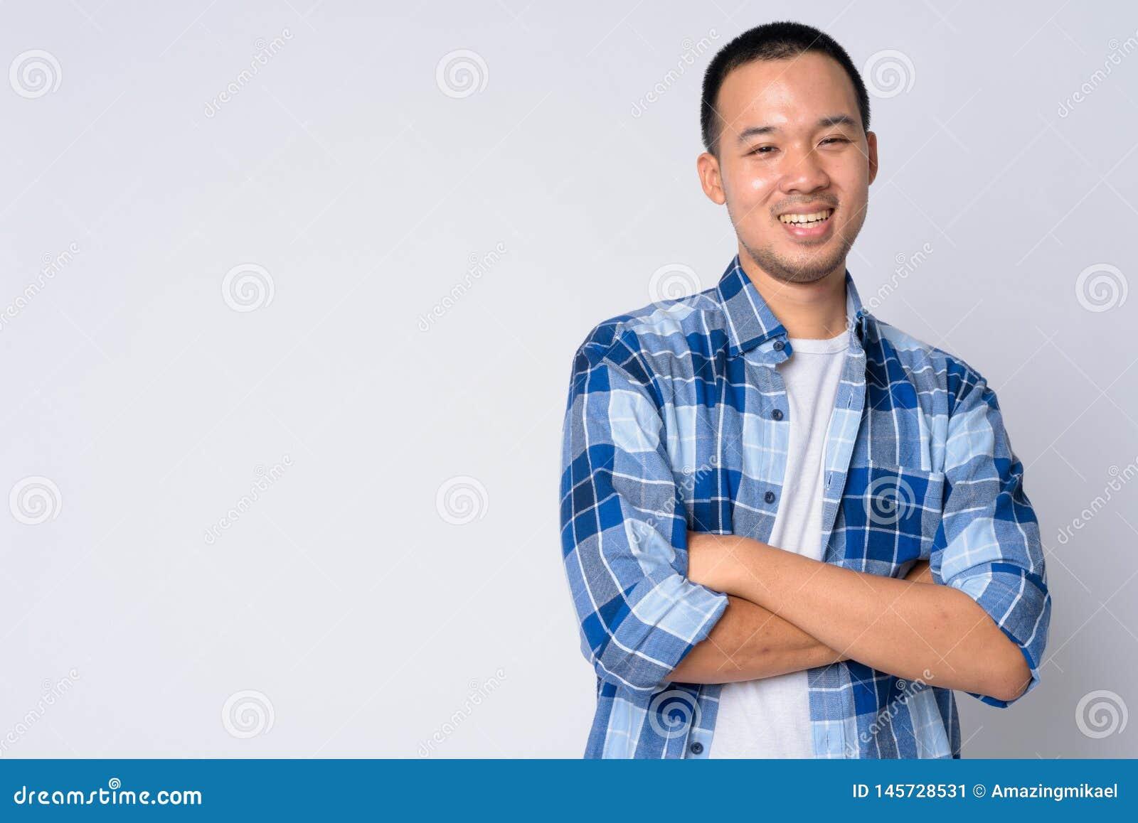 Ritratto di giovane uomo asiatico felice dei pantaloni a vita bassa che sorride con le armi attraversate