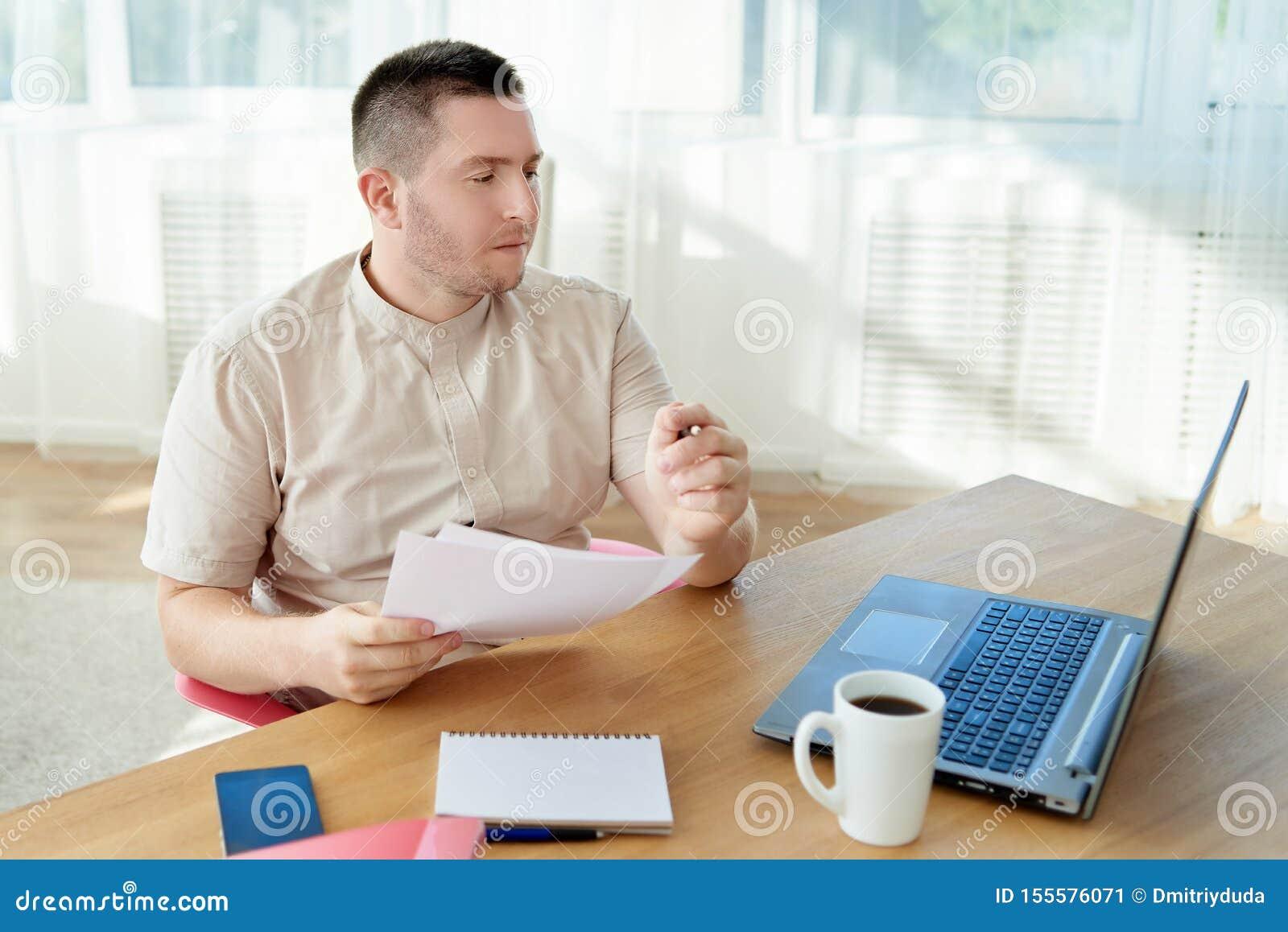 Ritratto di giovane uomo d affari sicuro che si siede allo scrittorio di legno e che lavora con i documenti e computer portatile