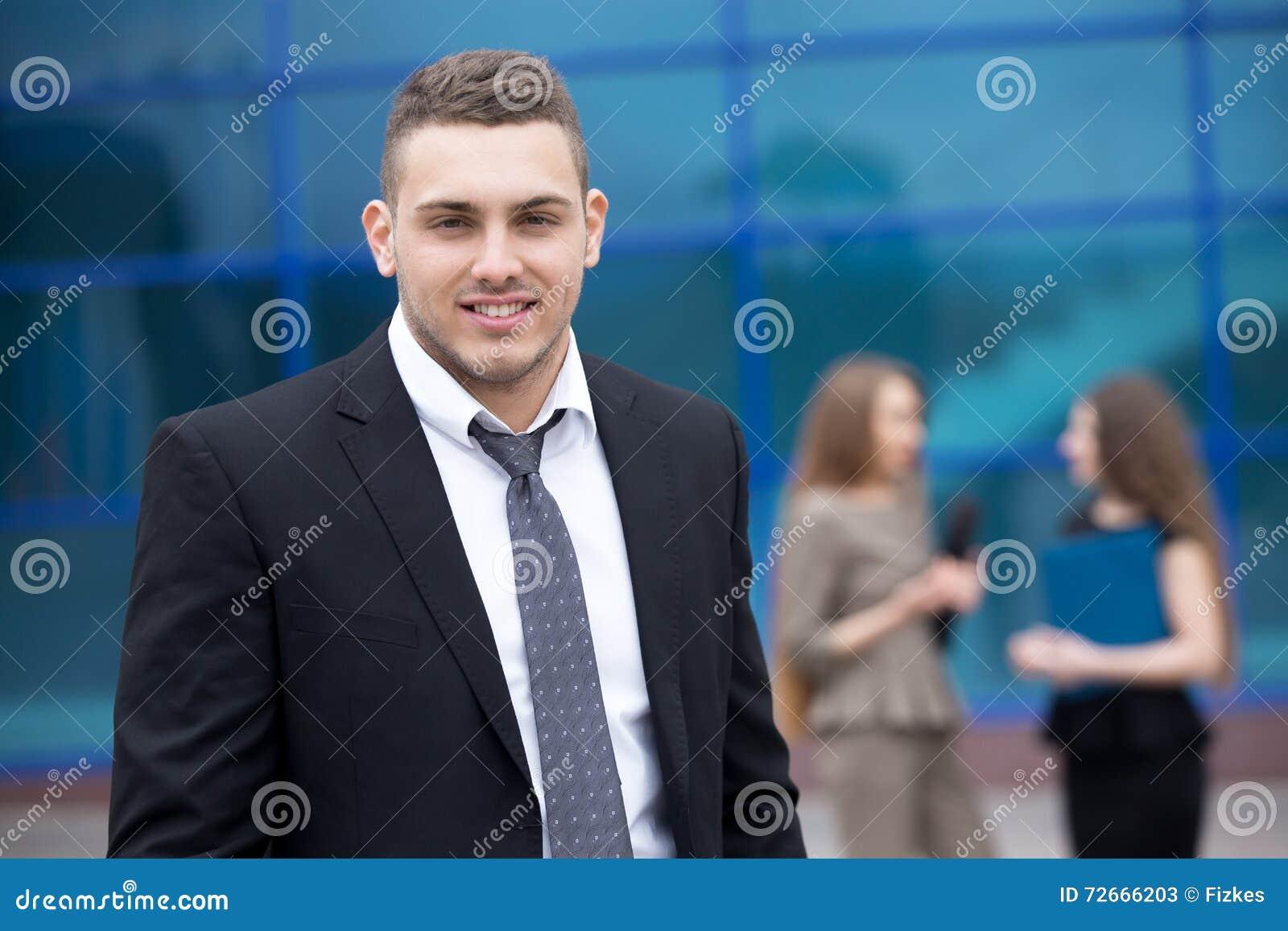 Ritratto di giovane uomo di affari che esamina macchina fotografica