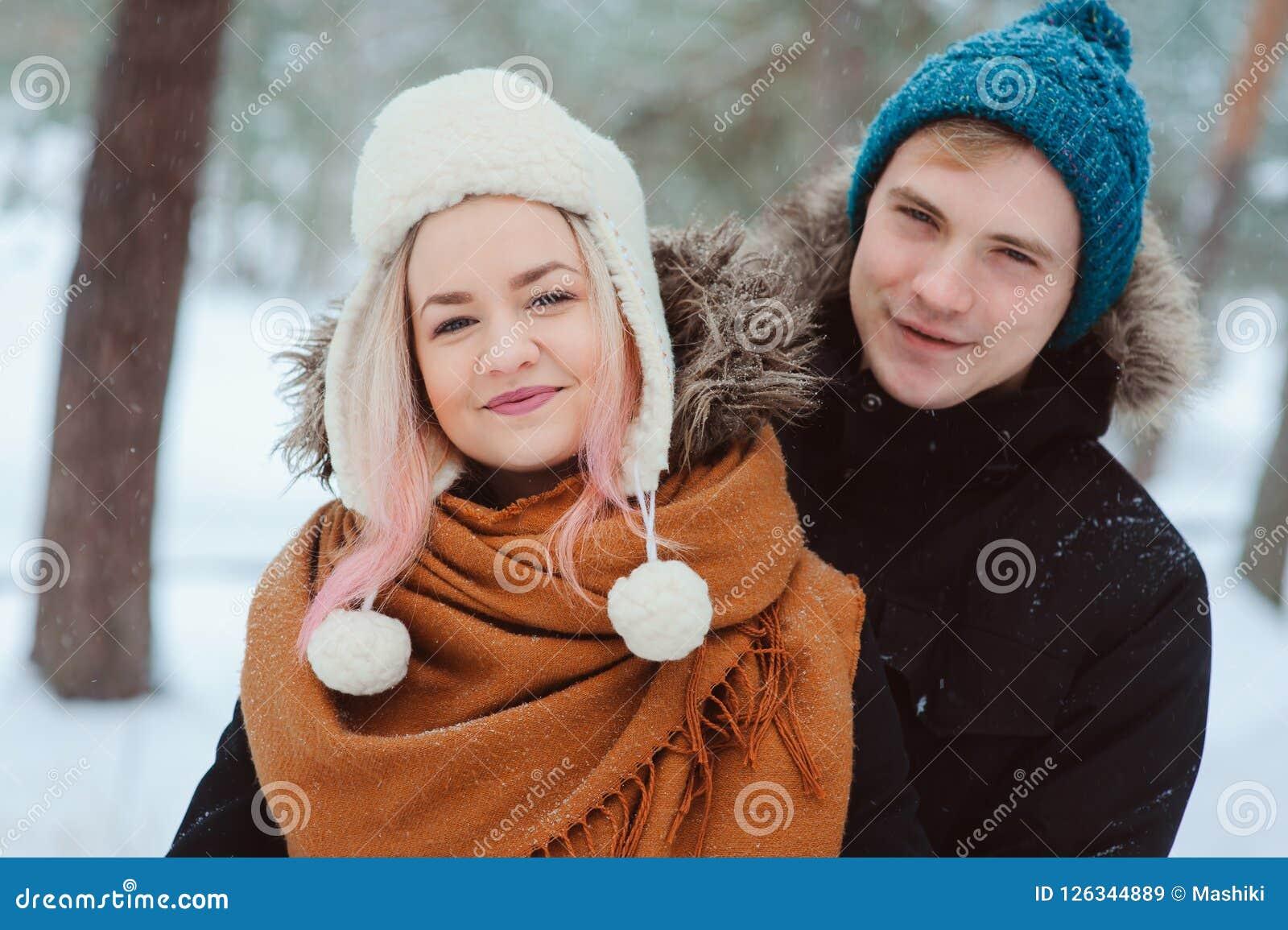 Ritratto di giovani coppie felici che camminano nella foresta nevosa di inverno