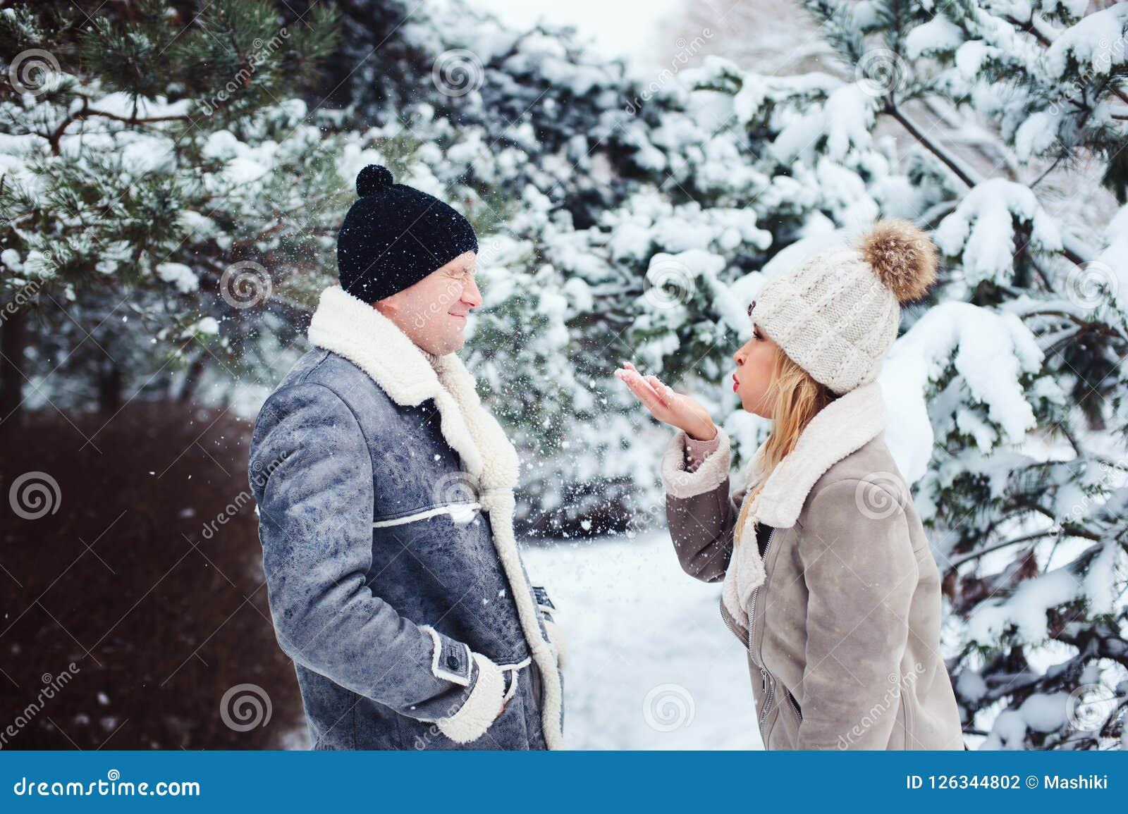 Ritratto di inverno delle coppie felici neve di salto, che giocano e spendere buon giorno all aperto nella foresta nevosa