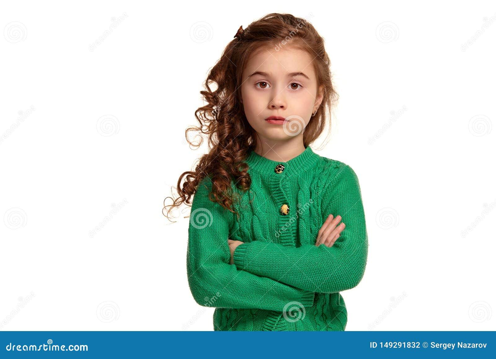 Ritratto di piccola ragazza castana con una posa dei capelli lunghi e ricci isolata su fondo bianco