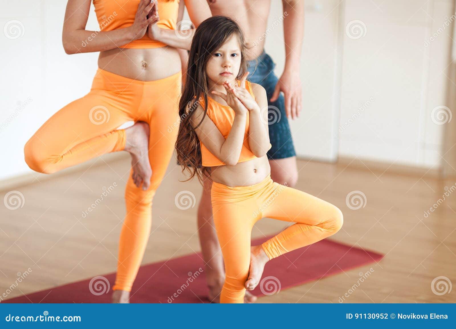 Ritratto di piccola yoga di pratica sorridente sveglia della ragazza, in un vestito arancio, facente yoga